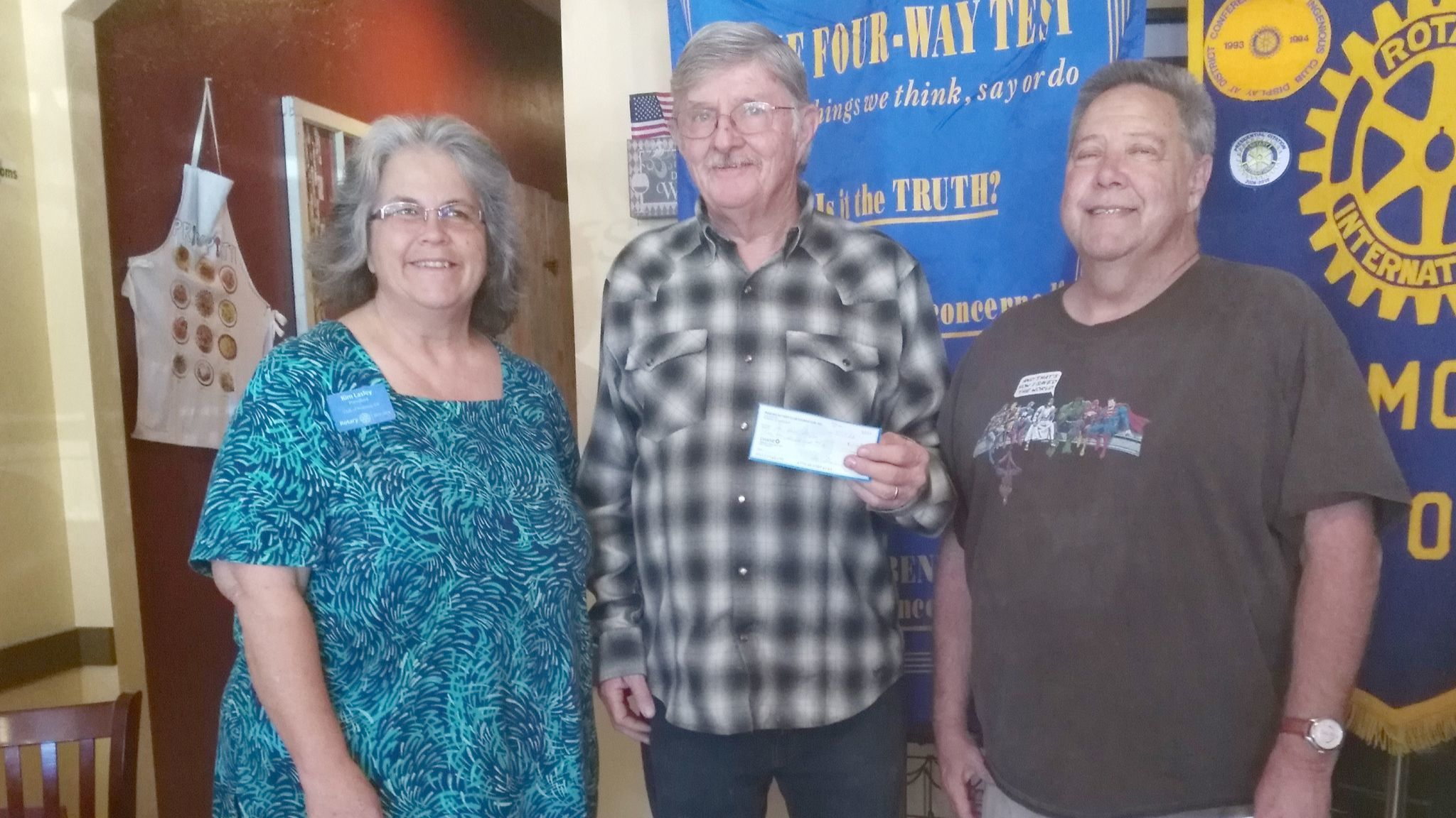 Bob Denny and Dave Richardson accept a $200 check from Ramona Rotary Club President Kim Lasley. The donation for In His Steps Recovery was made on behalf of the Rotary Club.