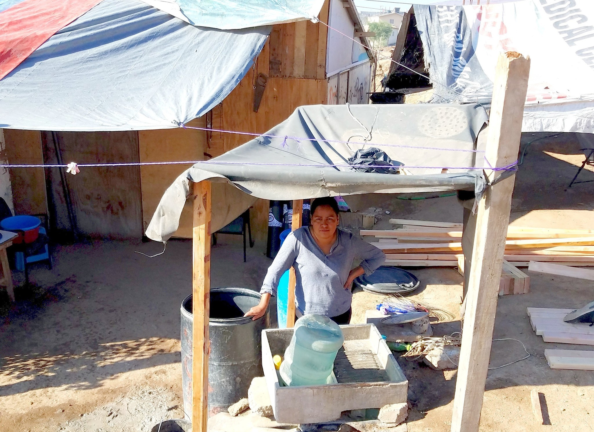 A photo taken by Schniepp shows how the families typically live prior to the Rotary Club home build. This woman poses in what functions as the home's kitchen.