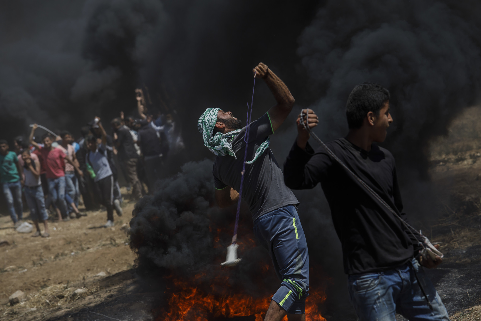 GAZA CITY, GAZA — MONDAY, MAY 14, 2018: Protesters fling projectile at the border fence separating