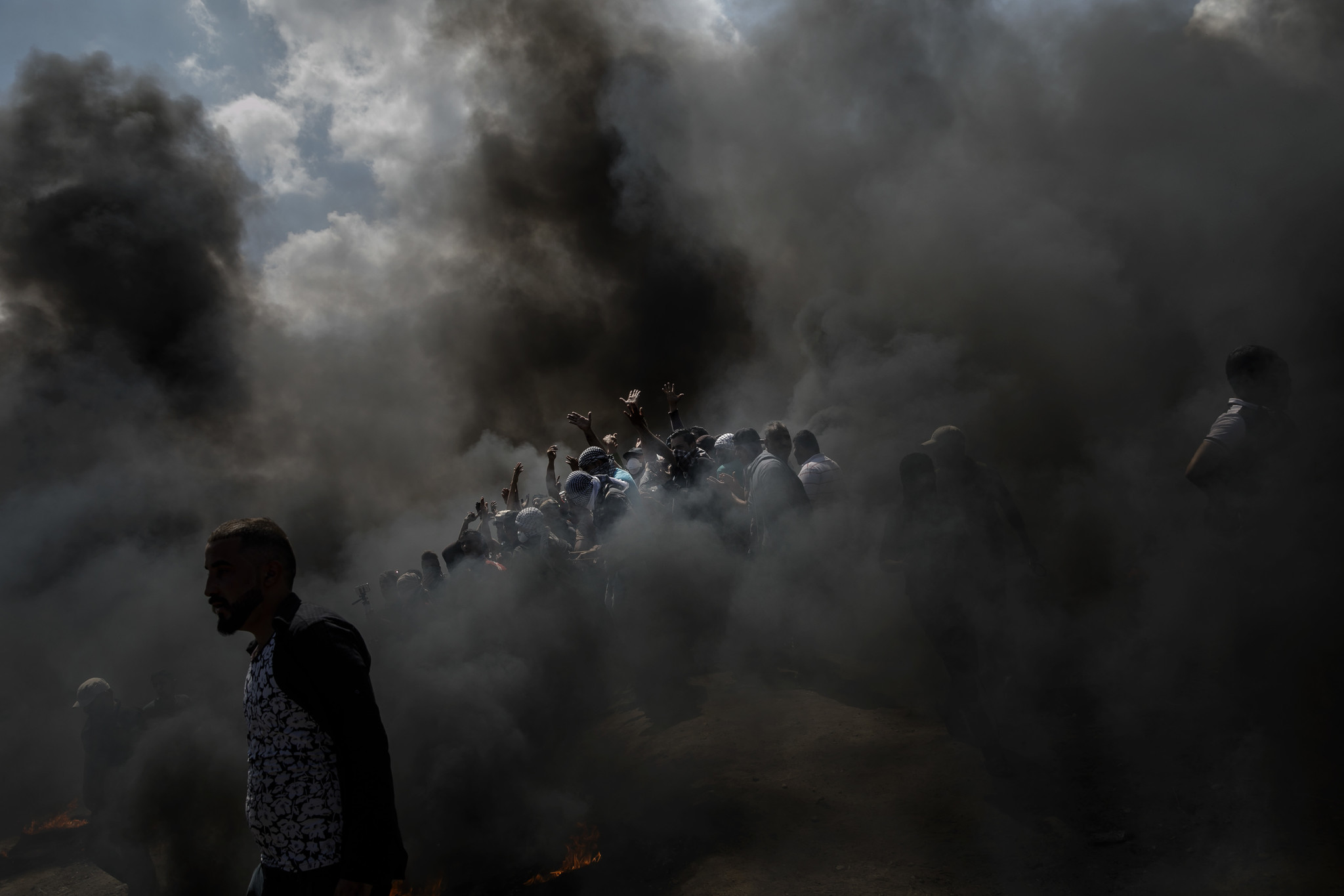 GAZA CITY, GAZA — MONDAY, MAY 14, 2018: Palestinians gather around to cheer and chant as they burn