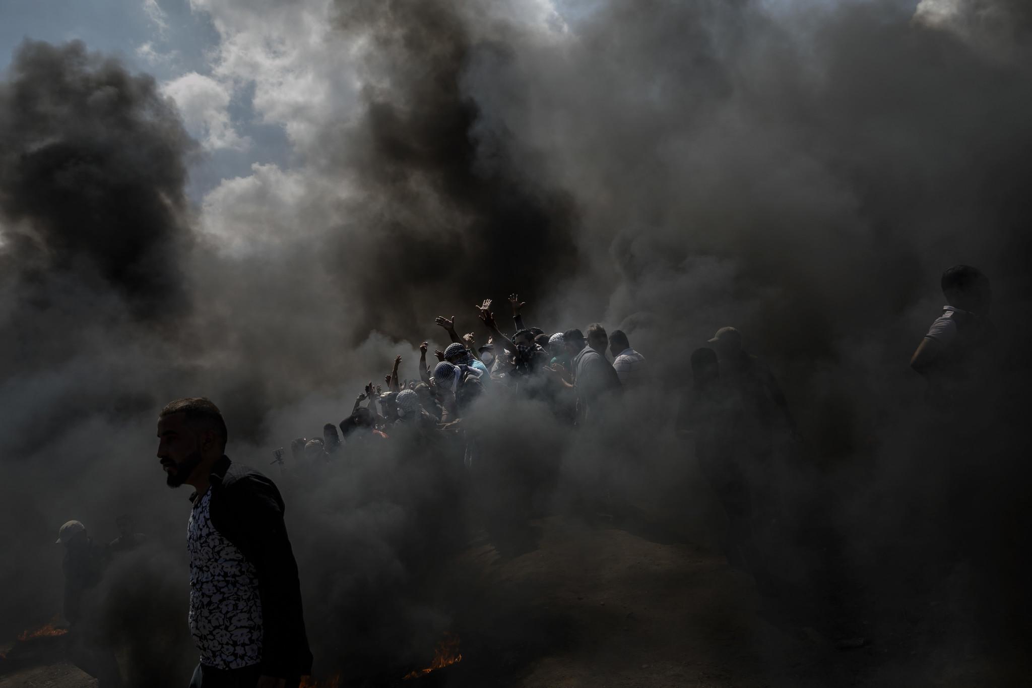 GAZA CITY, GAZA — MONDAY, MAY 14, 2018: Palestinians gather around to cheer and chant as they burn