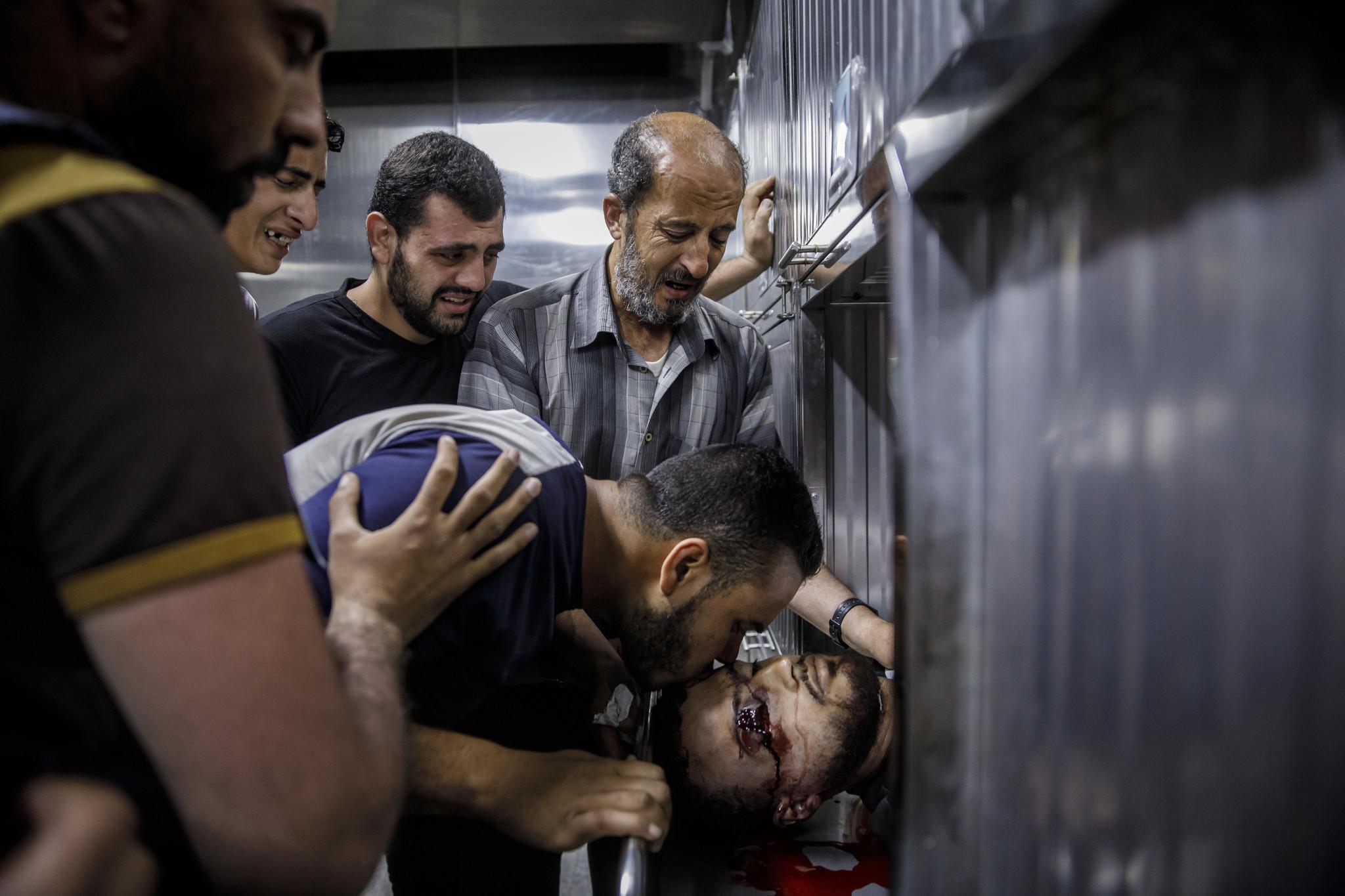 GAZA CITY, GAZA — MONDAY, MAY 14, 2018: Ibraheem Mohammed Al-Tubassi, father, top, and othe family