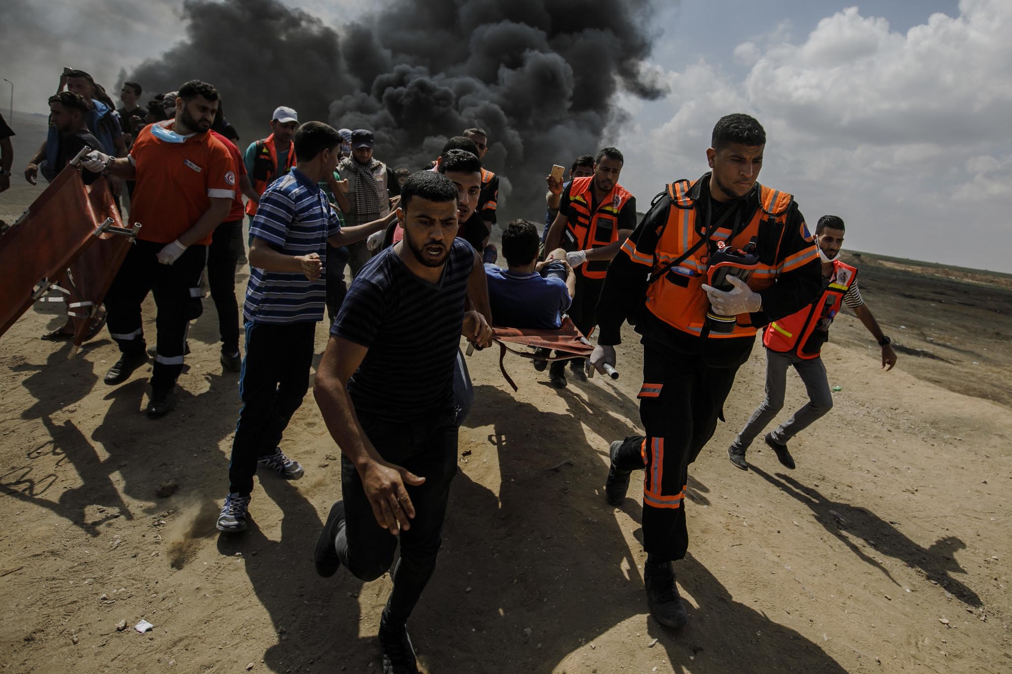 GAZA CITY, GAZA — MONDAY, MAY 14, 2018: Medical units carry away a wounded Palestinian shot by Isra