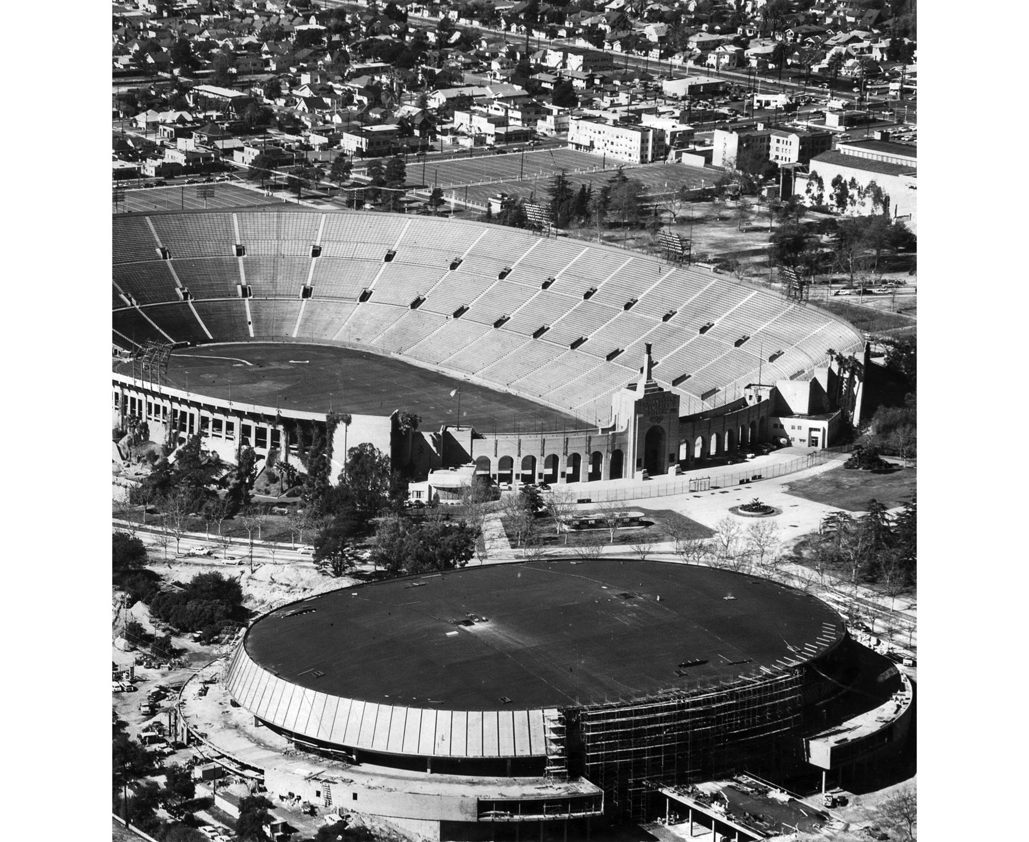 Early 1959: The Los Angeles Memorial Sports Arena under construction, foreground, with the Memorial