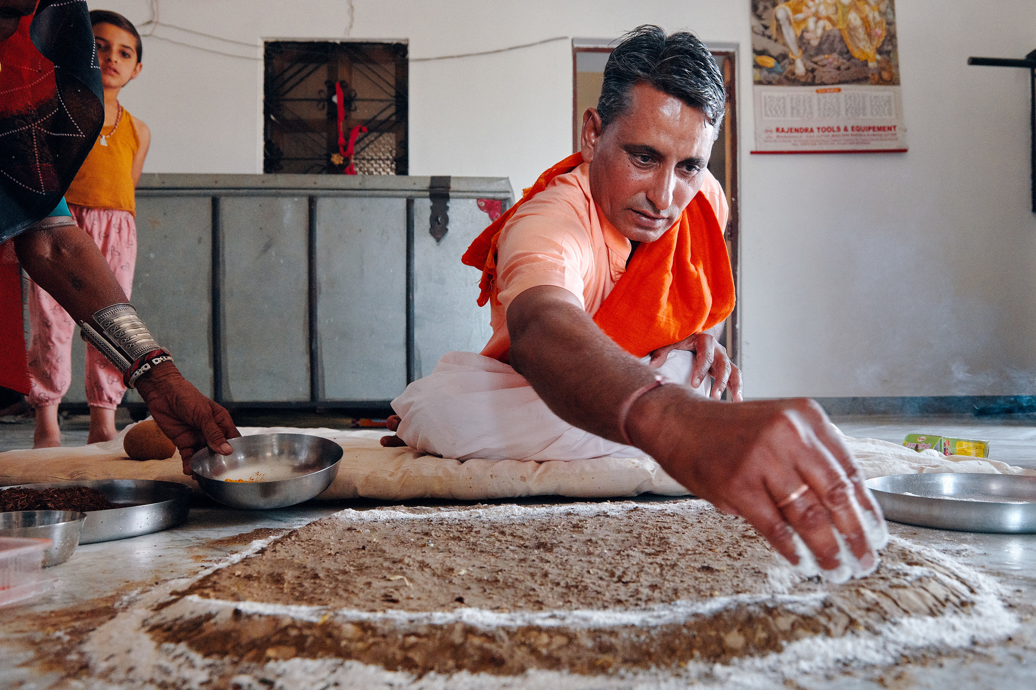 The head priest from the temple preparing for an evening prayer at the home of Hanuman Bishnoi in vi