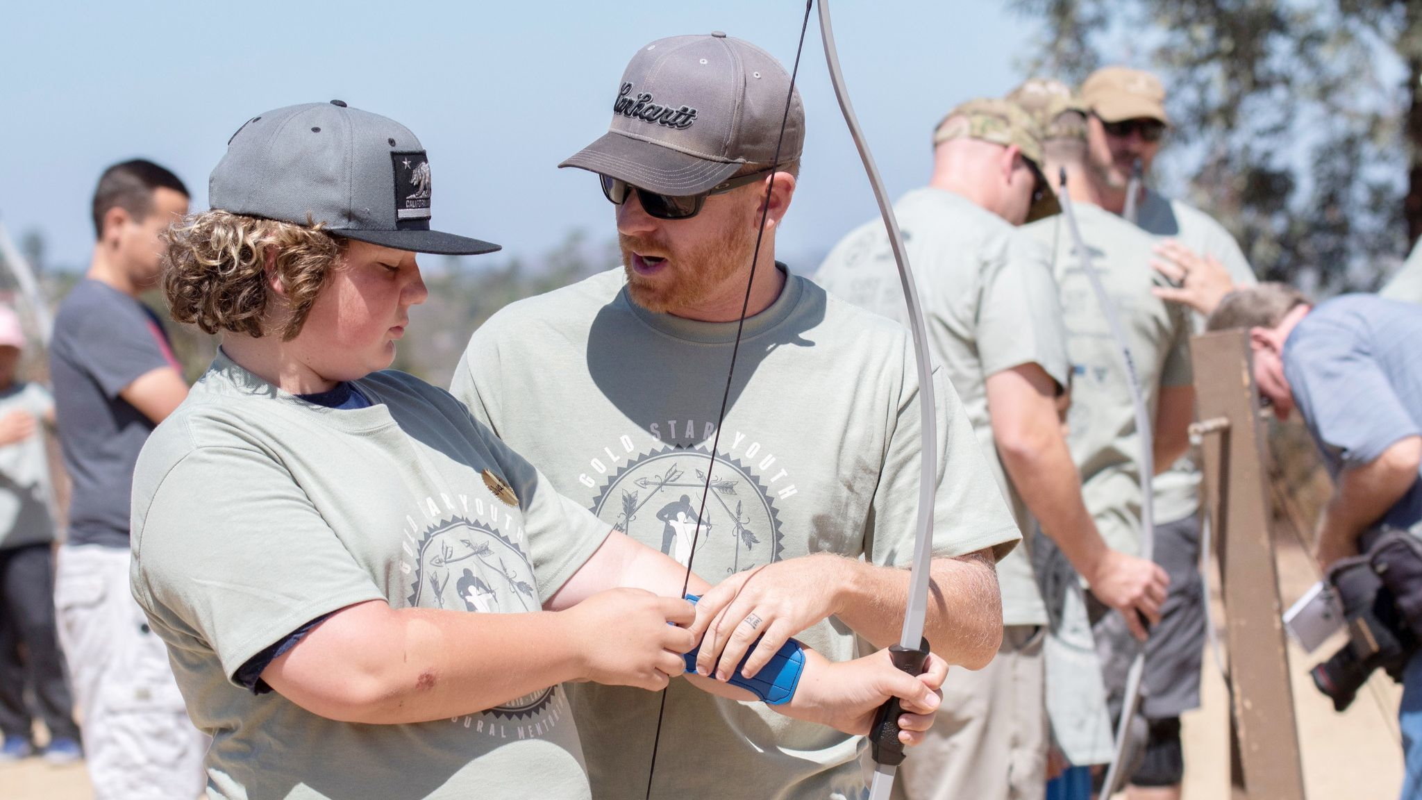 Wyatt Busby, left, gets a lesson in shooting arrows from mentor Wayne Gibson. Both were participating in The Special Liberty Project's mentoring at Lake Poway's archery range.