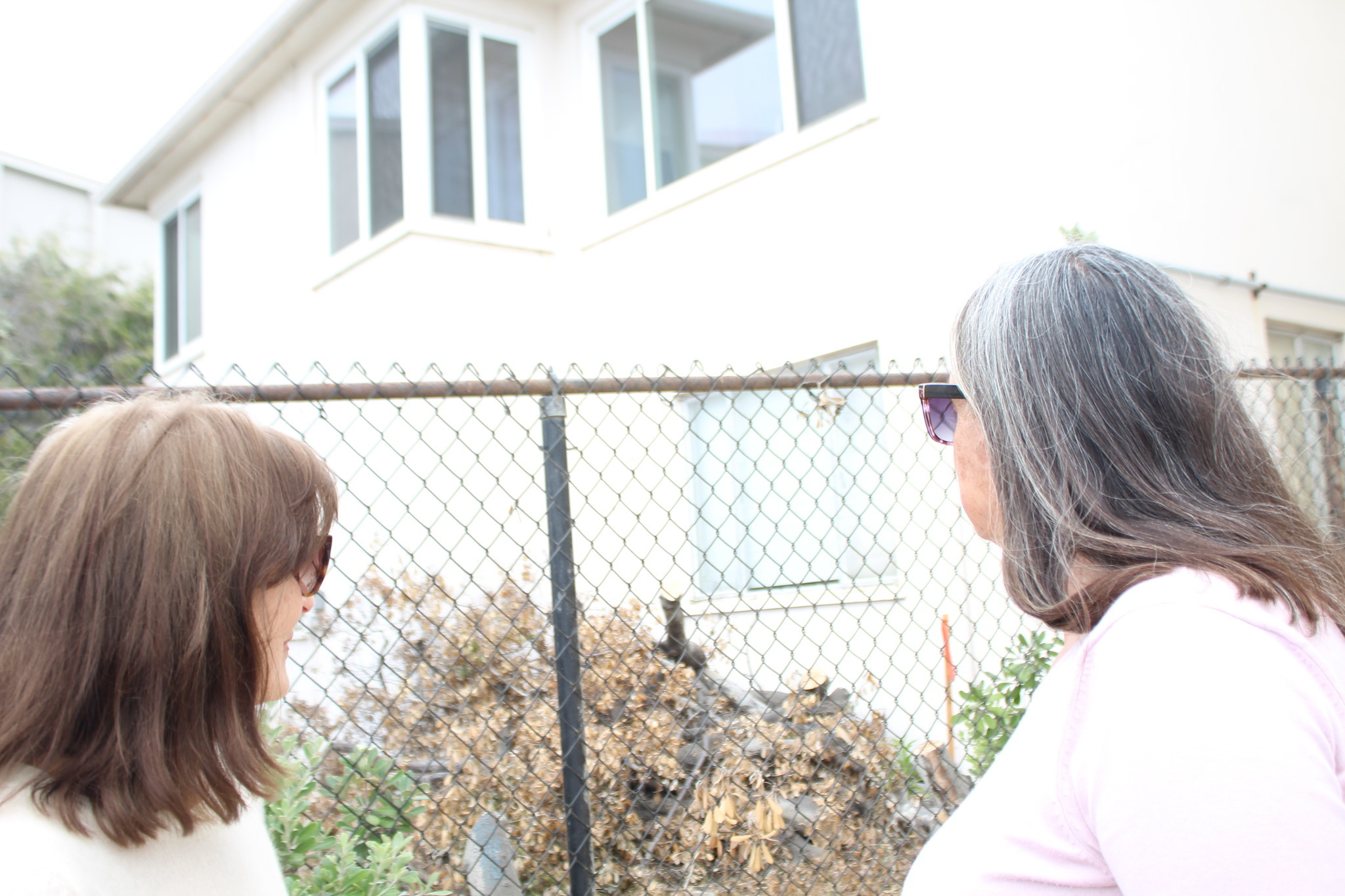Dawn and Ashley Farson stare up at the room over the backyard that formerly served as Richard Farson's study.