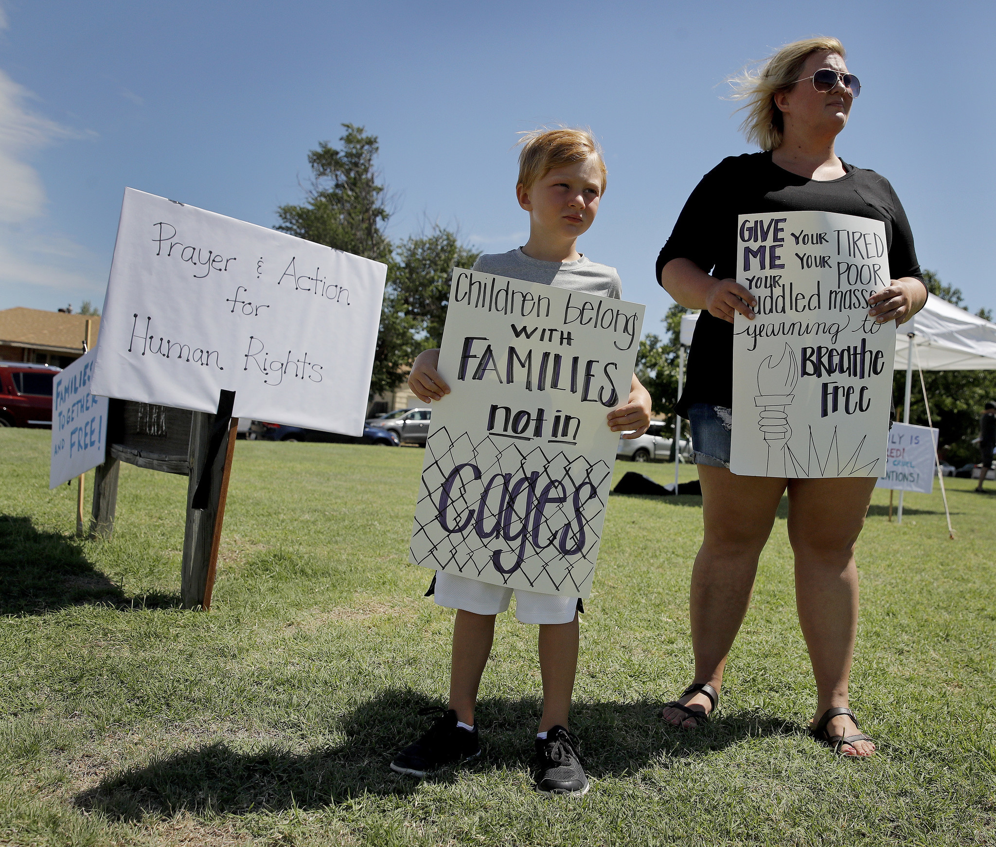Bennett Heeke, age 5, and his mother Sarah Doll Heeke hold signs at a rally protesting U.S. immigrat