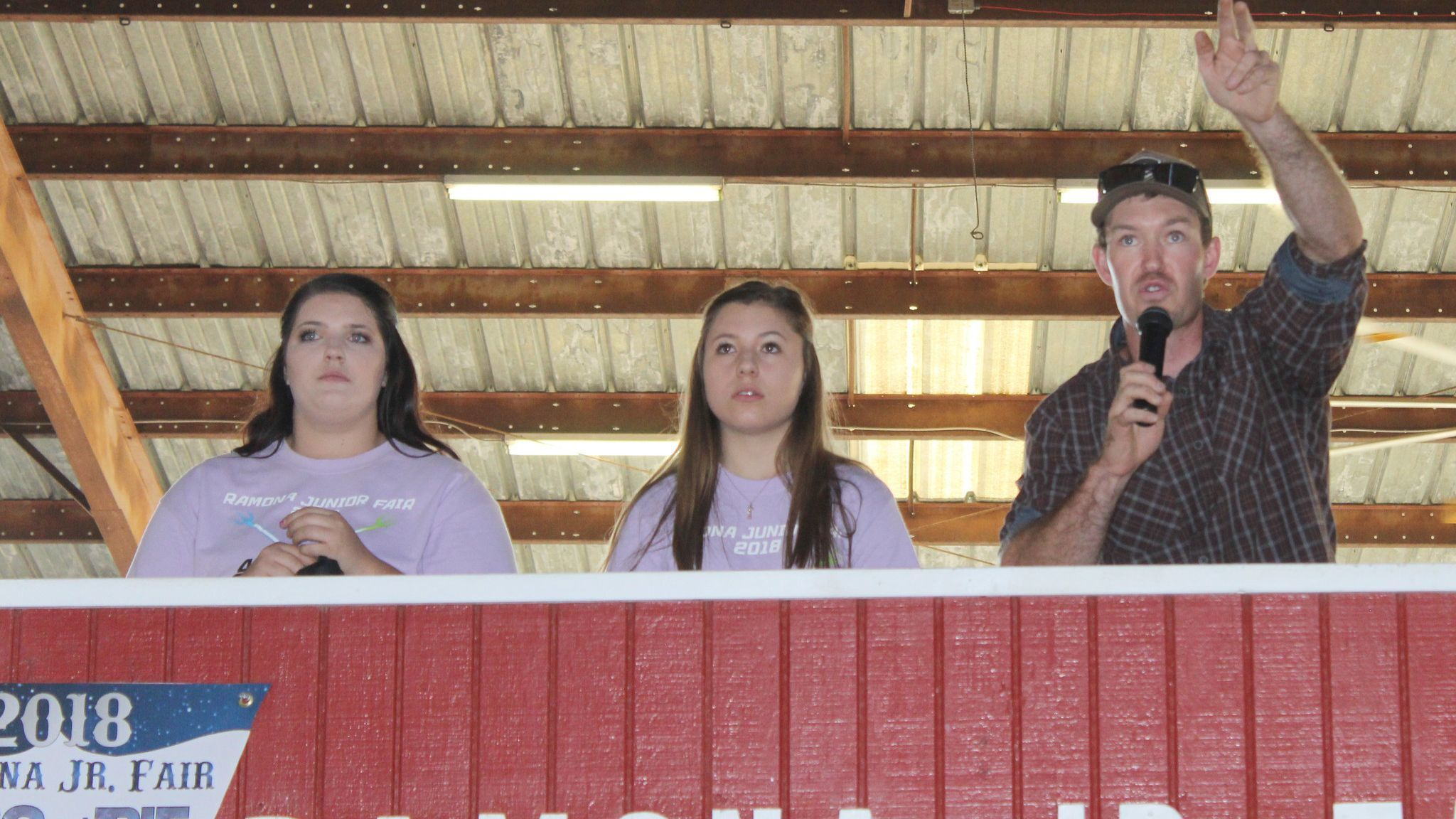 Auctioneer Brett Huff, former 4-H'er and 2011 Ramona High graduate, encourages higher bids. Assisting him are Alyssa van Tol, 4-H representative, and Catalina Gonzalez, FFA rep.