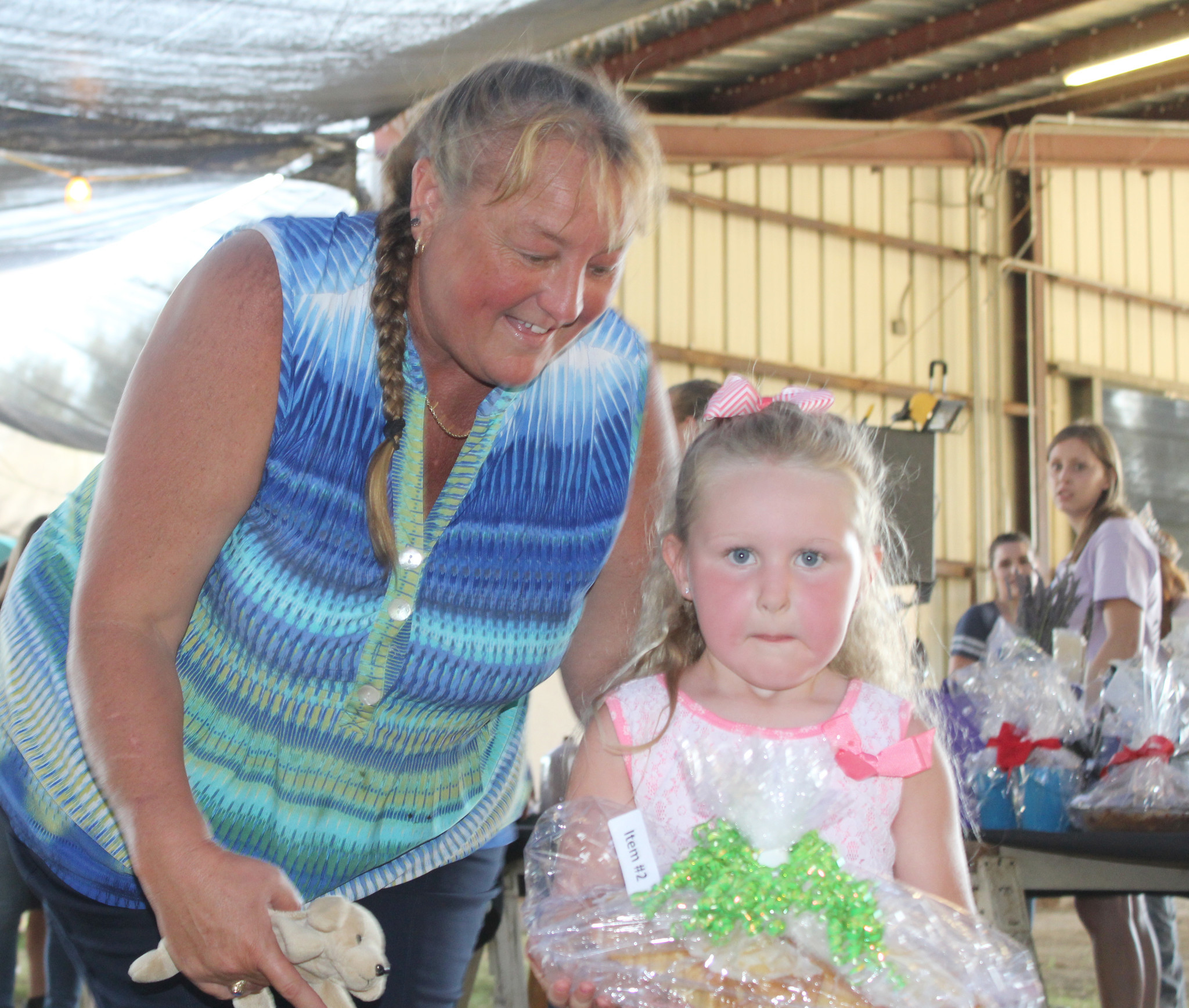 Assisted by her aunt, Crissy Tobiason, Kendall Blackburn, 4, carries a lemon pound cake to show bidders.