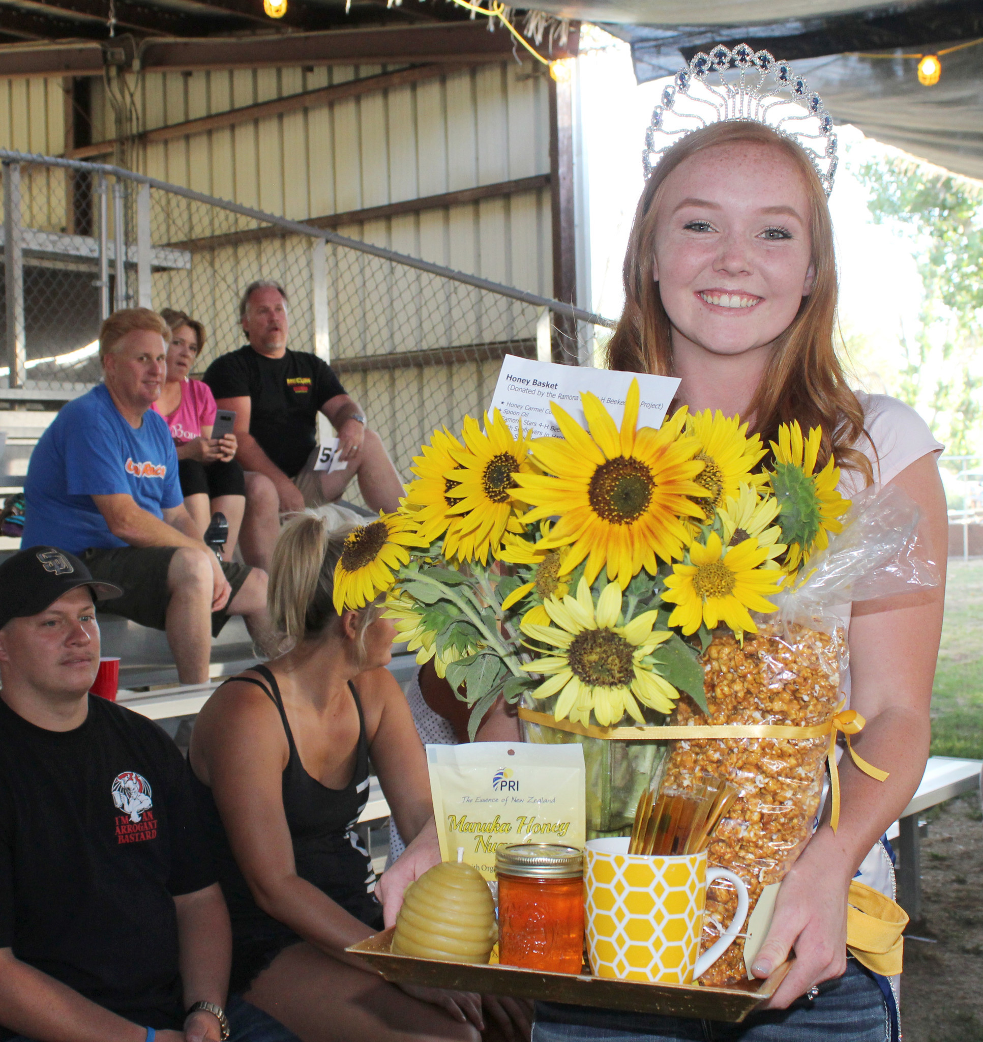 Miss Ramona Megan Kelly carries the colorful Honey Basket that Ramona Stars 4-H prepared for the auction. Sheila and Rich Swafford donated $380 for the basket.