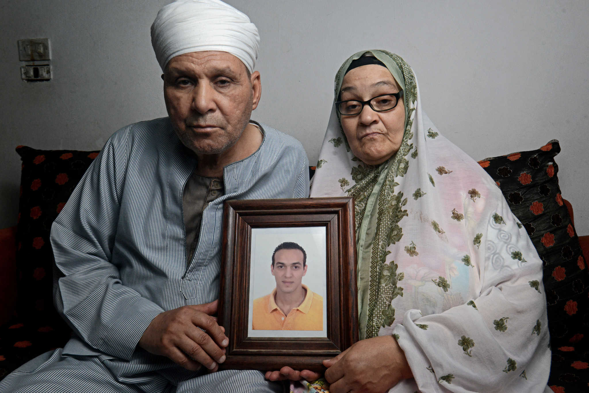 Shawkan's parent hold his portrait at their place in the Giza working class district of Faisal. July