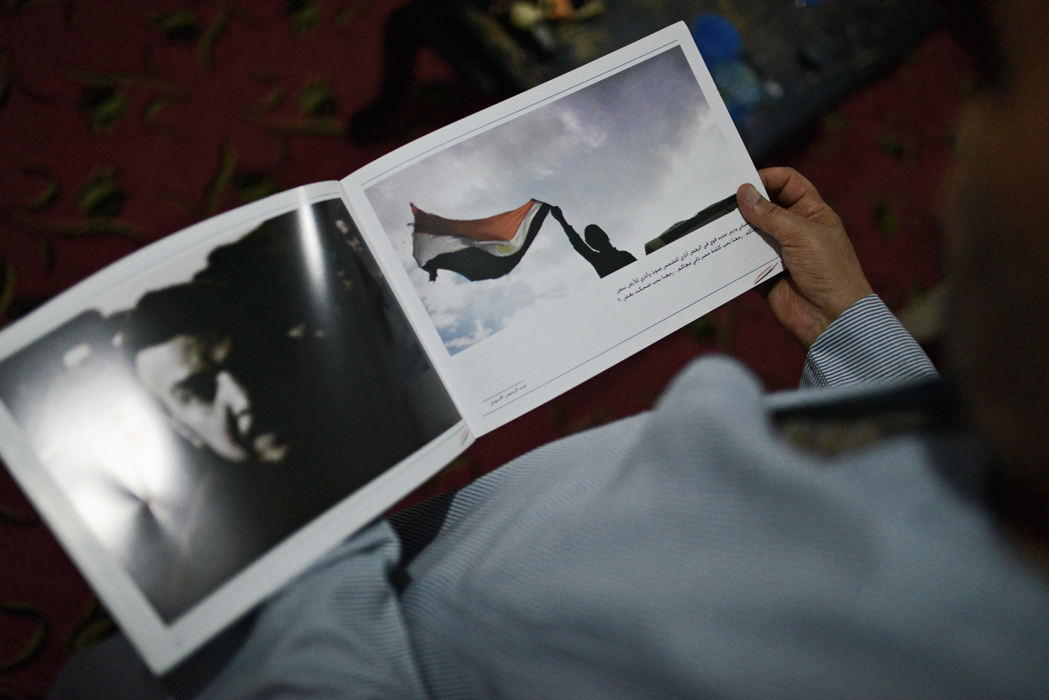 Shakwan's father holds a photo-book that contains his son's documentation of the 2011 Egyptian revol