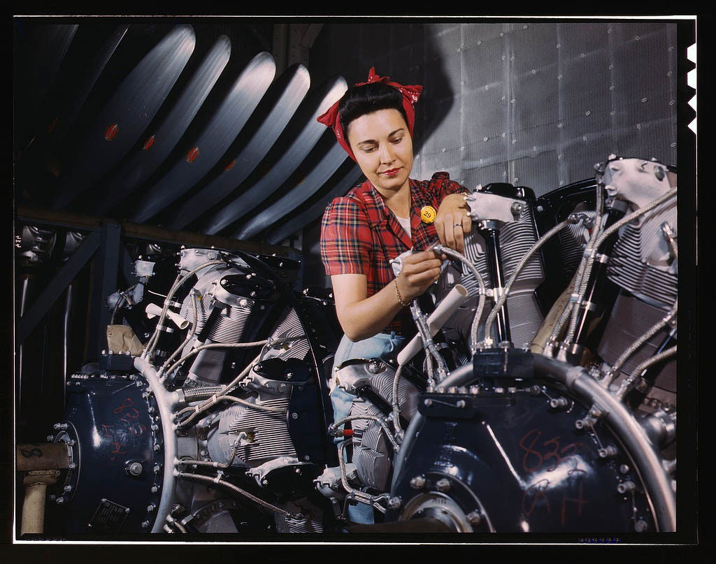 Woman working on an airplane motor at North American Aviation, Inc., plant in Inglewood, Calif. June