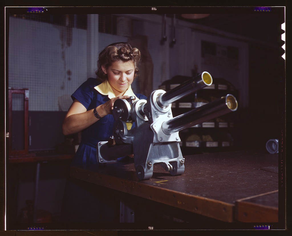 A young female employee of North American Aviation, Incorporated, working over the landing gear mecha