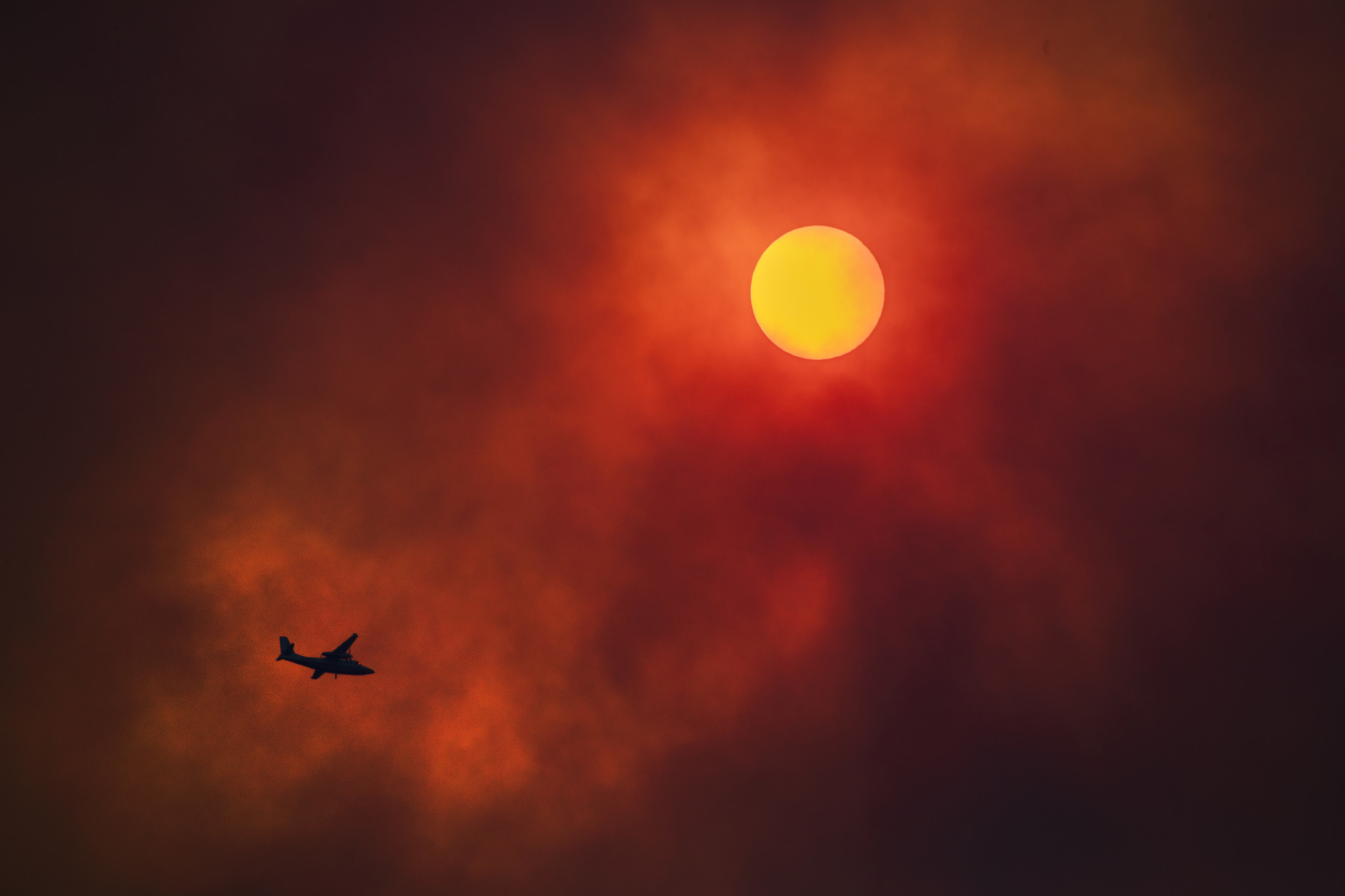 LAKE ELSINORE, CALIF. — TUESDAY, AUGUST 7, 2018: Heavy smoke obscures the sun as a fire aircraft wo