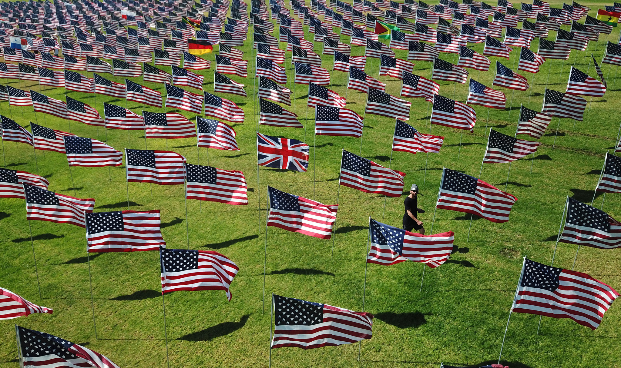 lawn of the 2,977 flags,—2,887 American flags for each American life lost and 90 international flags representing the home countries of individuals from abroad who died in the