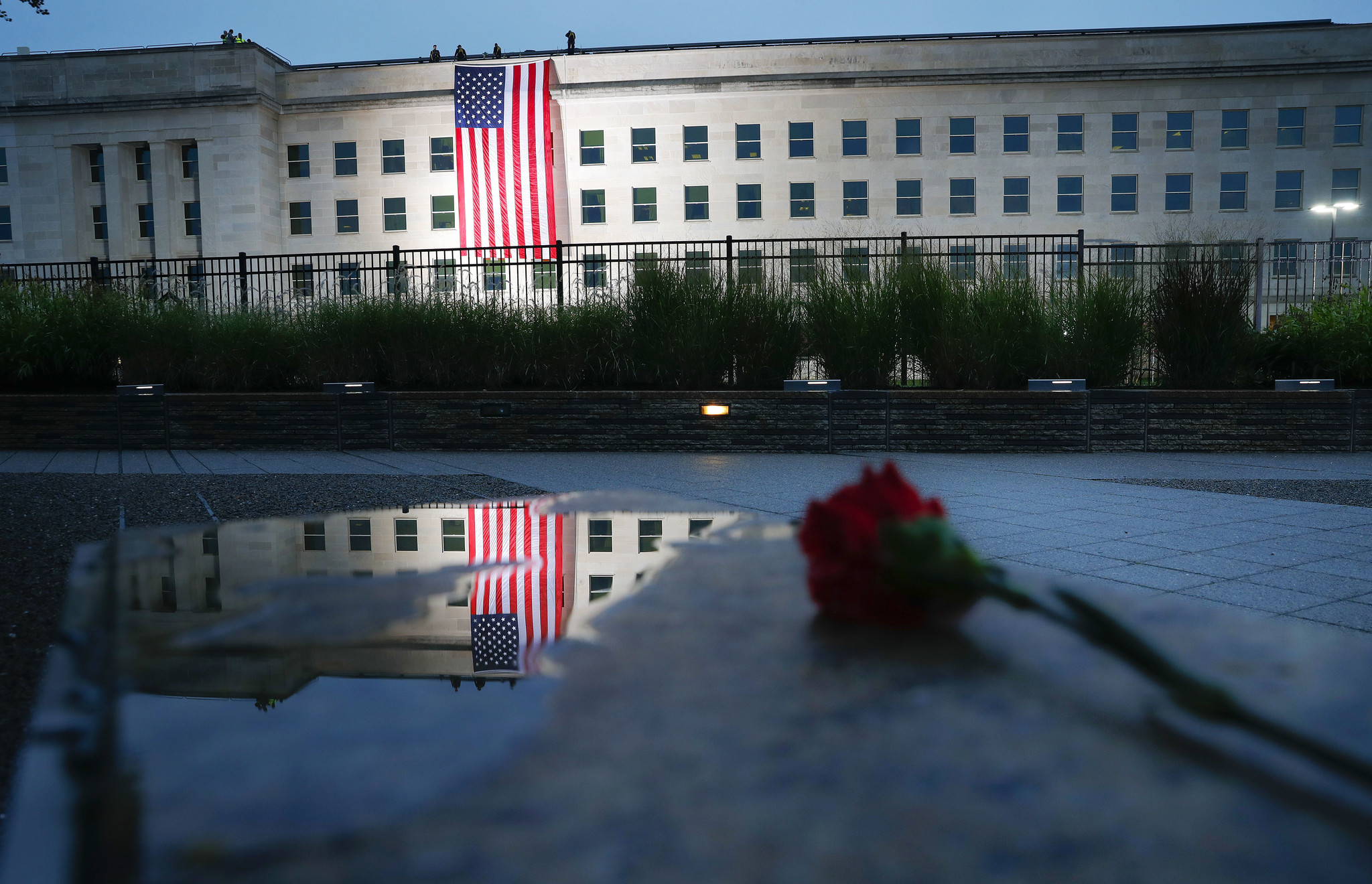 A U.S. flag is unfurled at sunrise on Tuesday, Sept. 11, 2018, at the Pentagon on the 17th anniversa