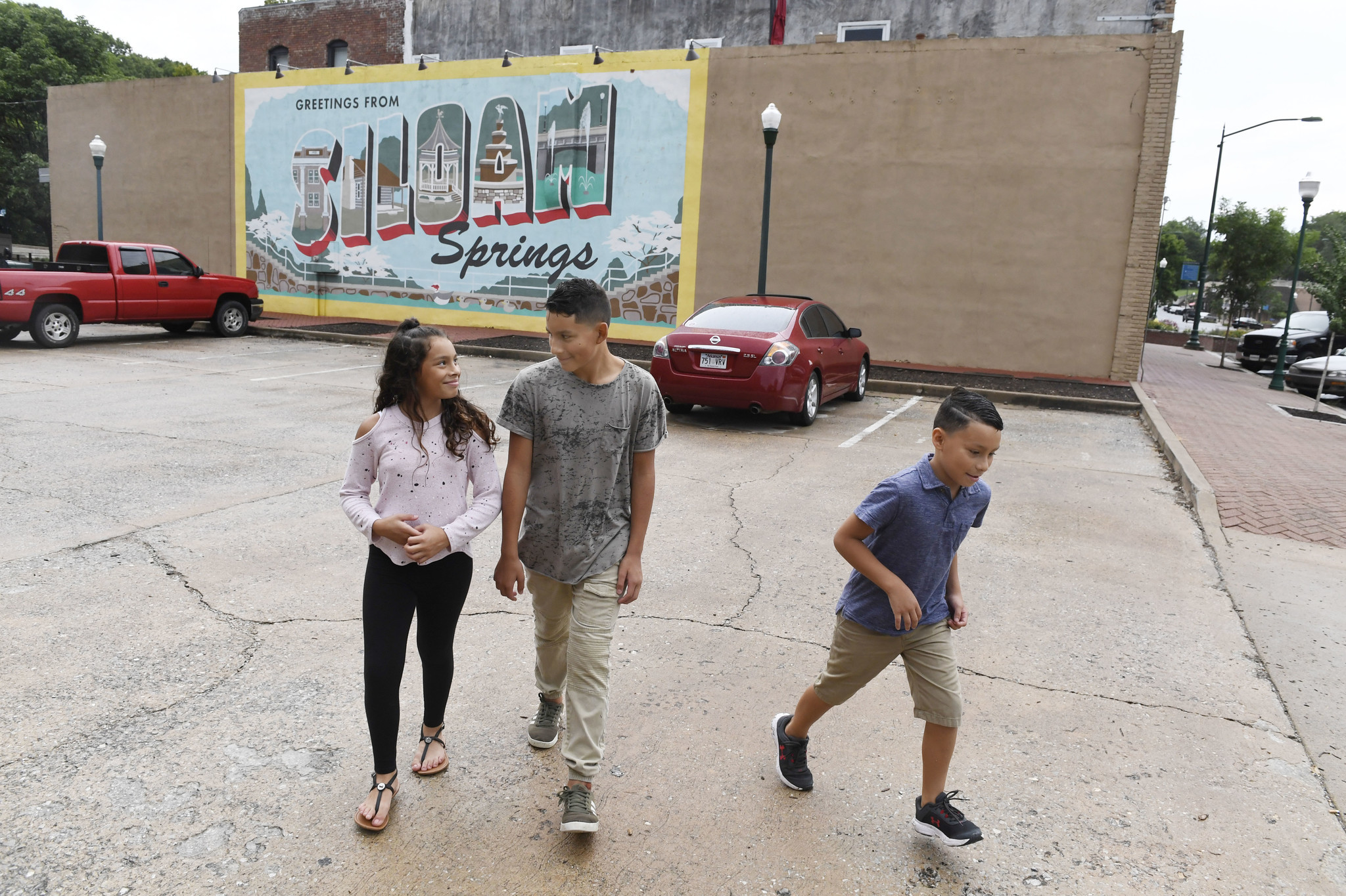 (Left to right) Dyanara Solis, 11, Dominic Solis, 12, and Dorian Solis, 8, walk through a parking lo