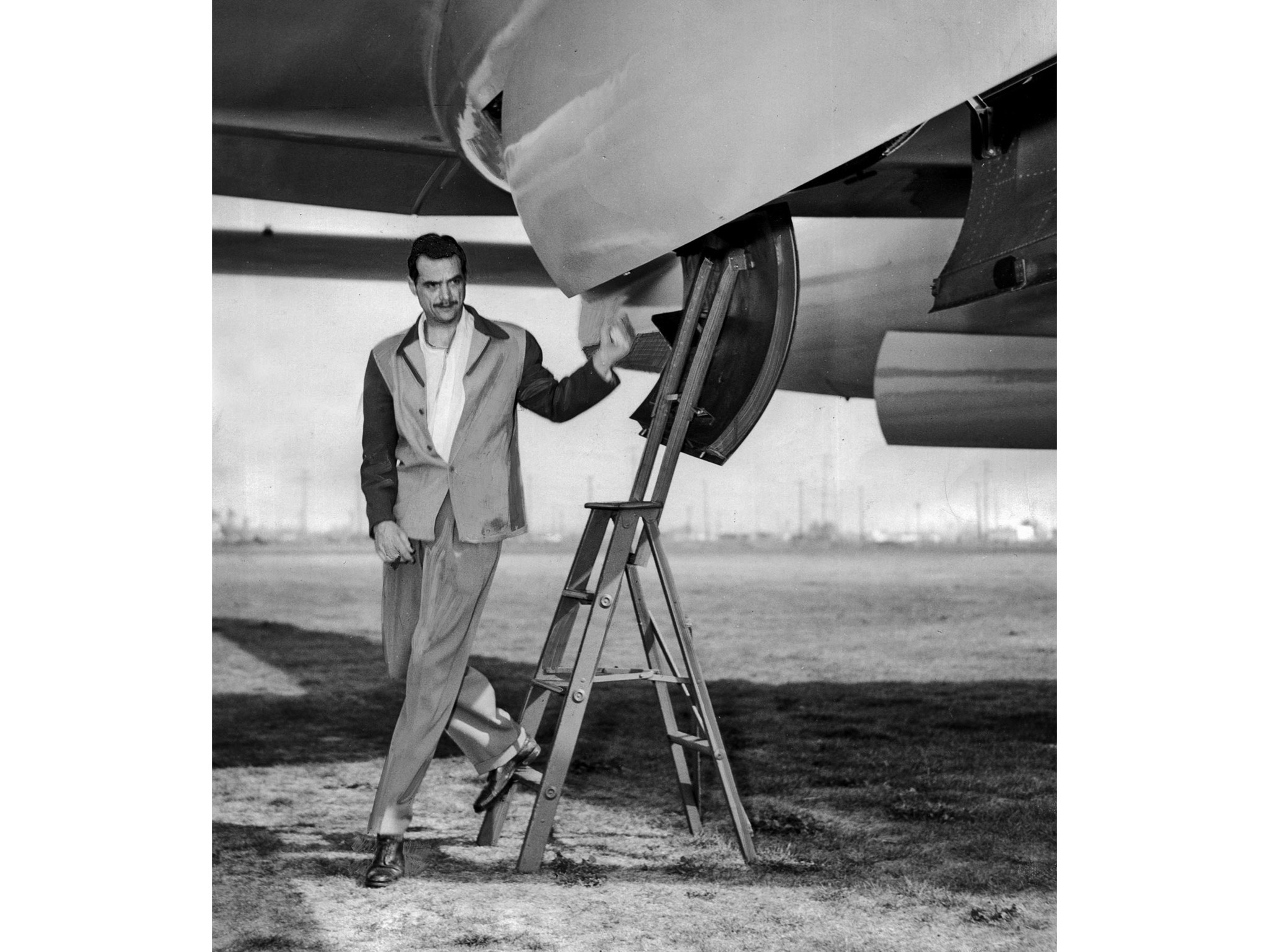 April 5, 1947 photo of Howard Hughes as he steps from plane he designed and built after making test