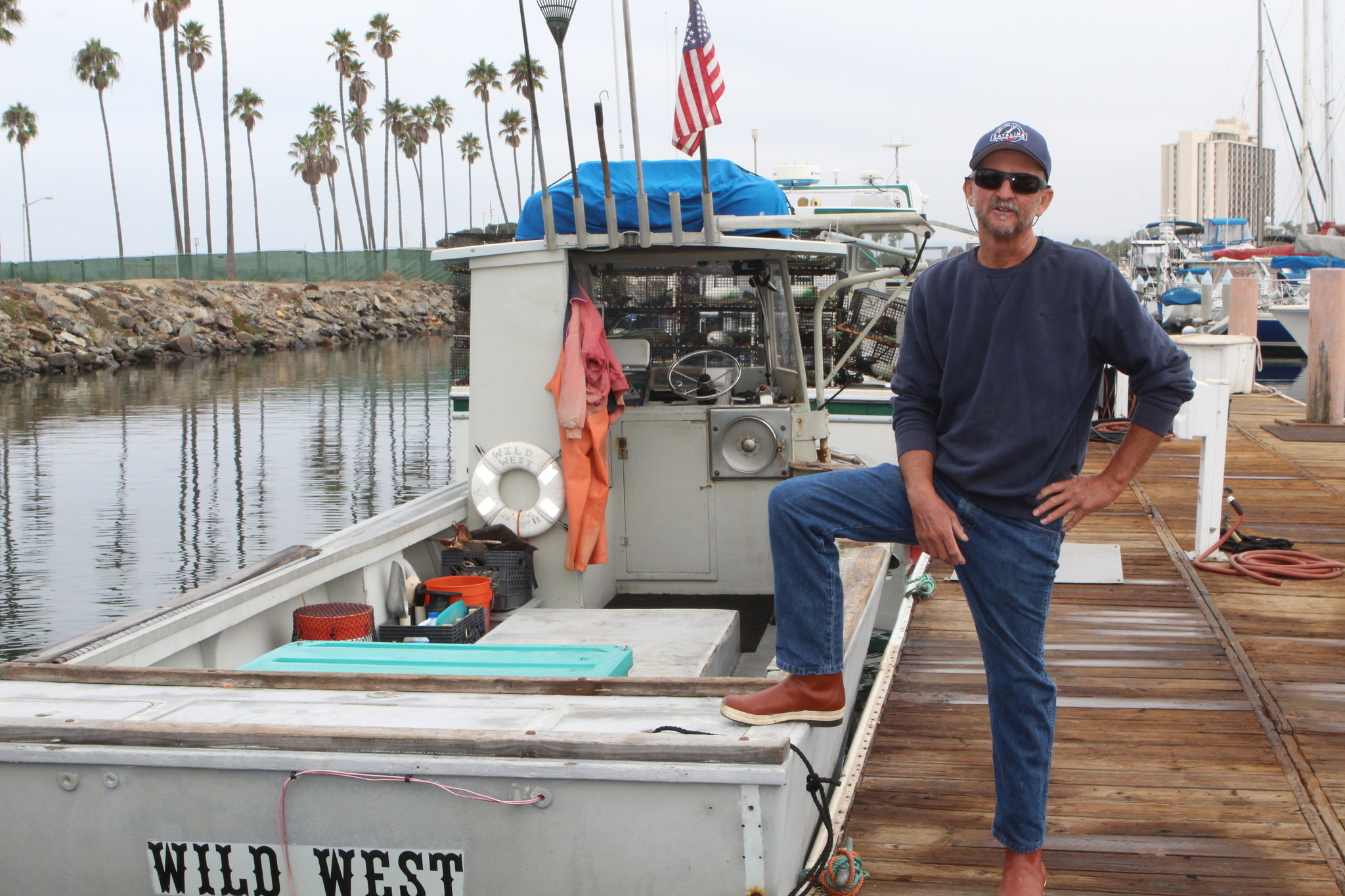 John Law poses next to the skiff, Wild West, which he's owned since 2000.