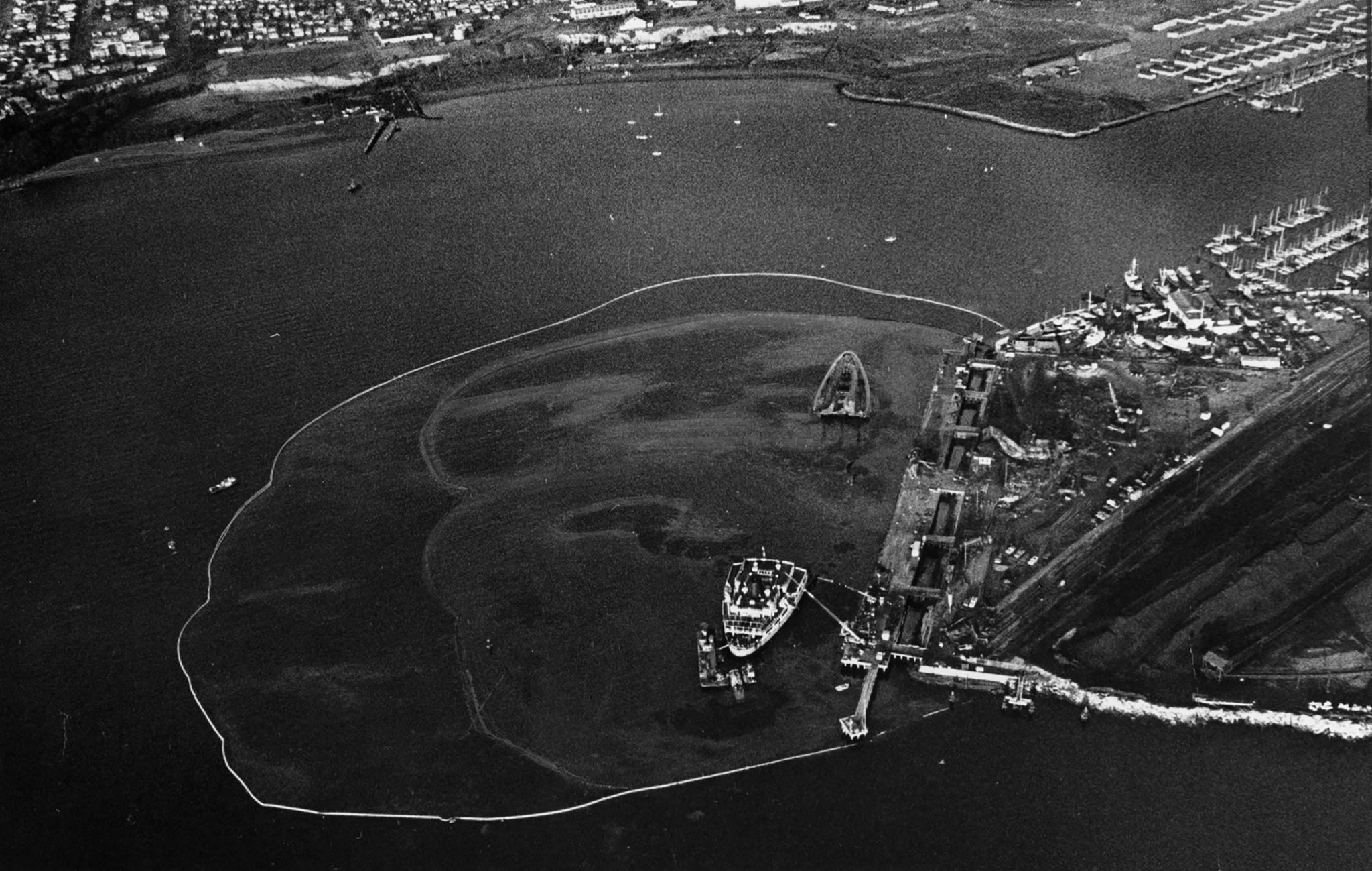 Dec. 28, 1976: Aerial view of the Sansinena wreckage with oil spill and containment equipment deploy