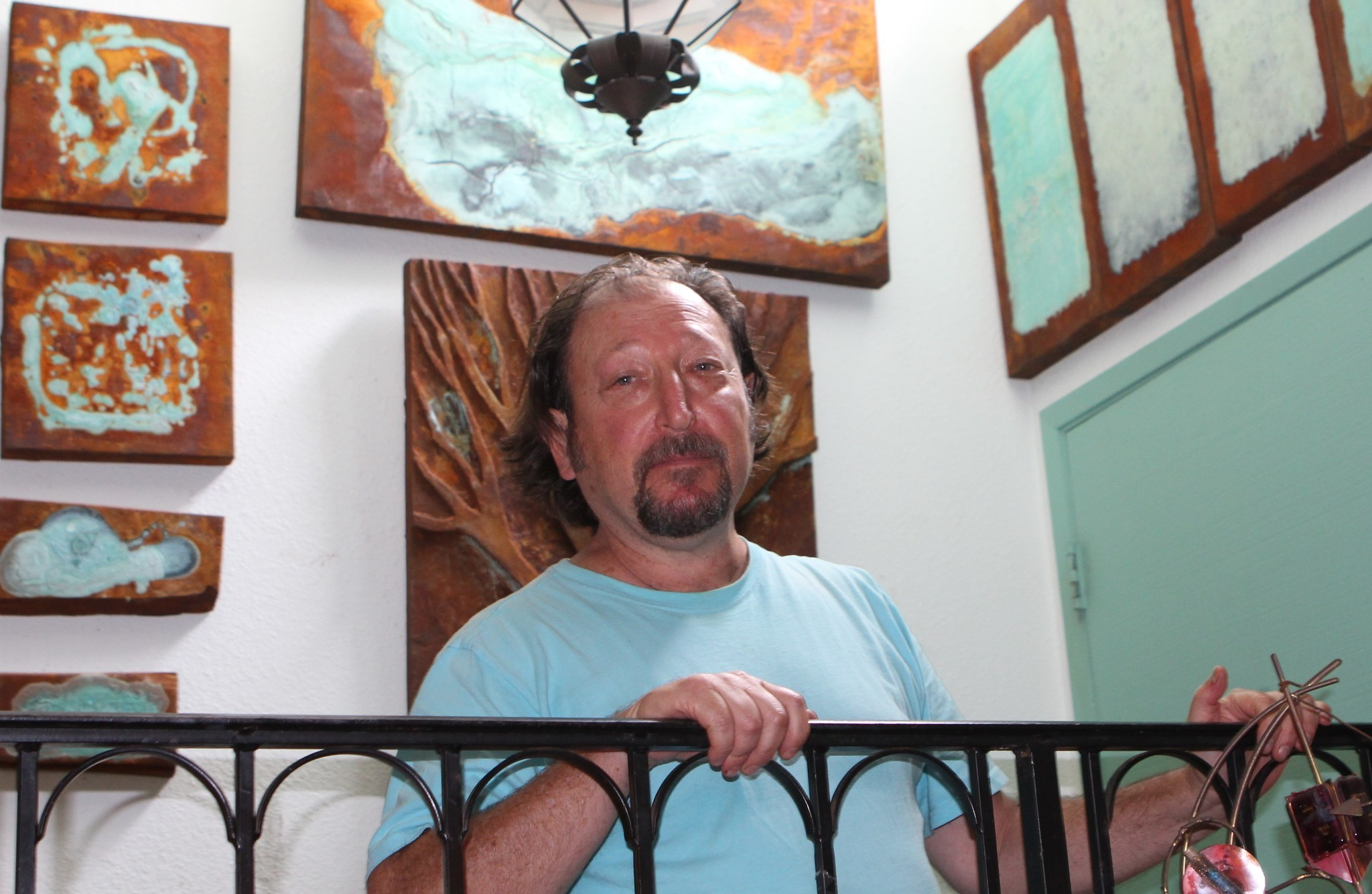 Ed Whitmore poses in his La Jolla condominium backdropped by his works of art.