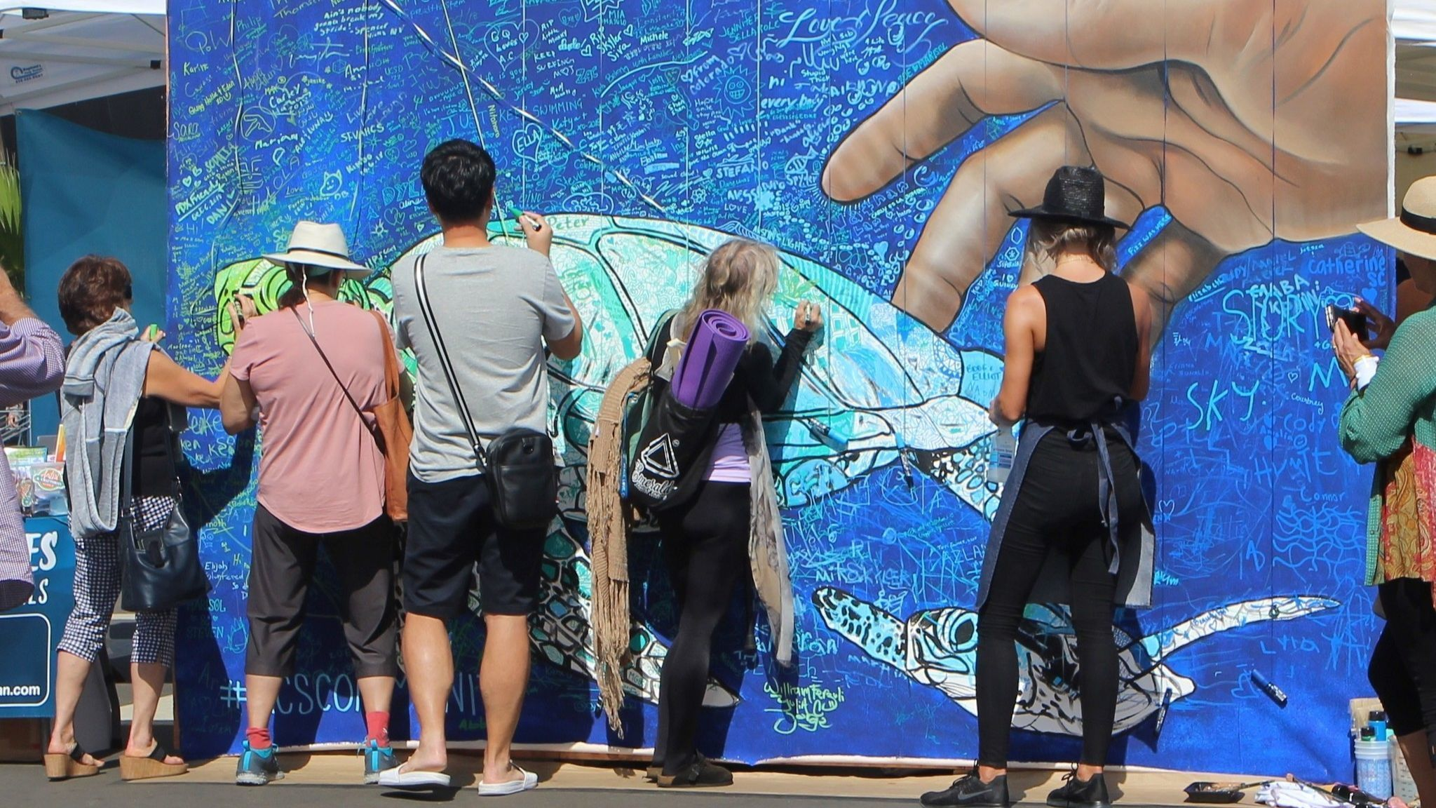 San Diego muralist Carly Ealey, right, leads members of the public in painting an interactive mural.