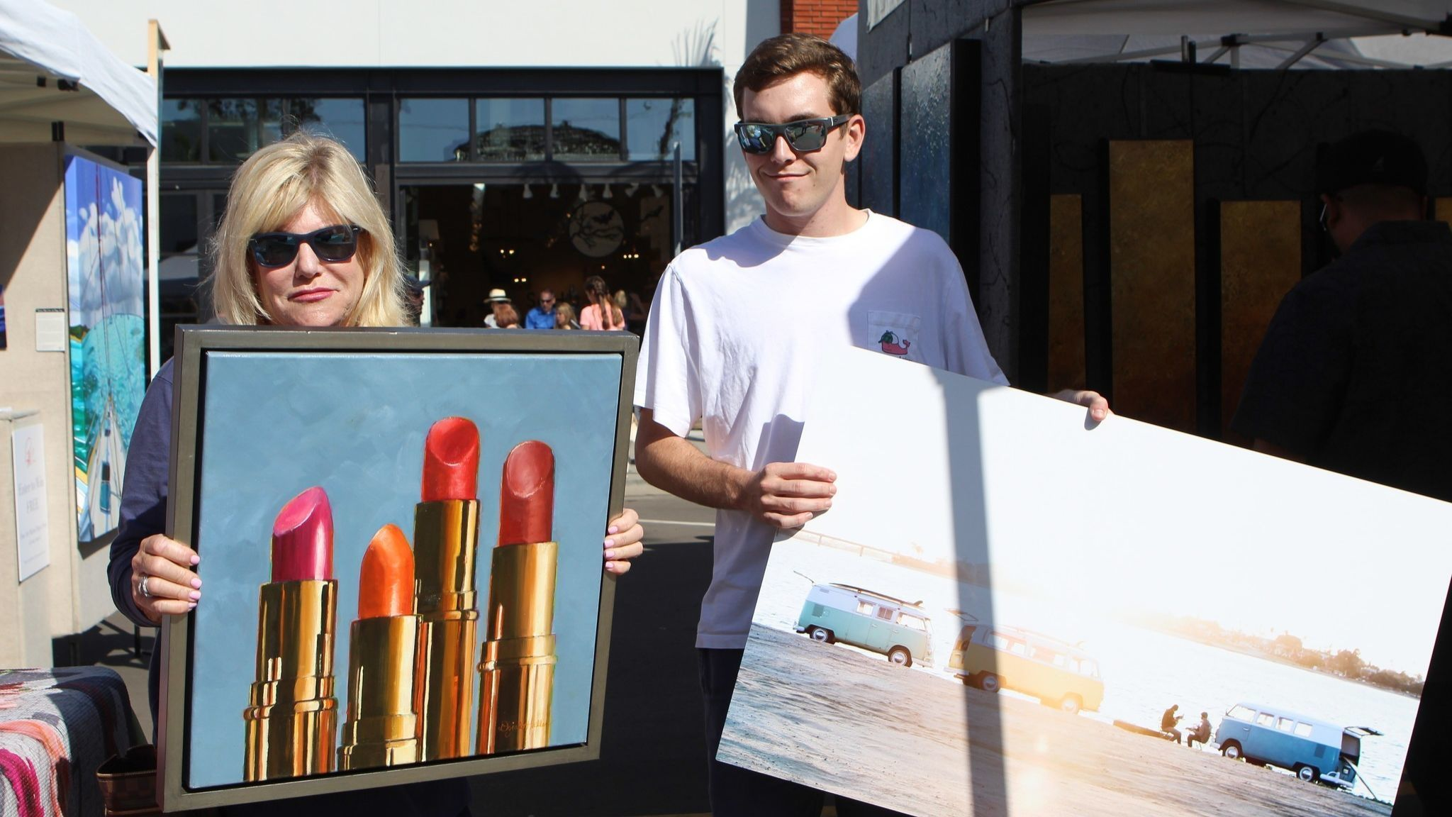 Former KFMB-TV news anchor Lorraine Hennessy poses with her son, Tom, and two pieces they purchased at the festival.