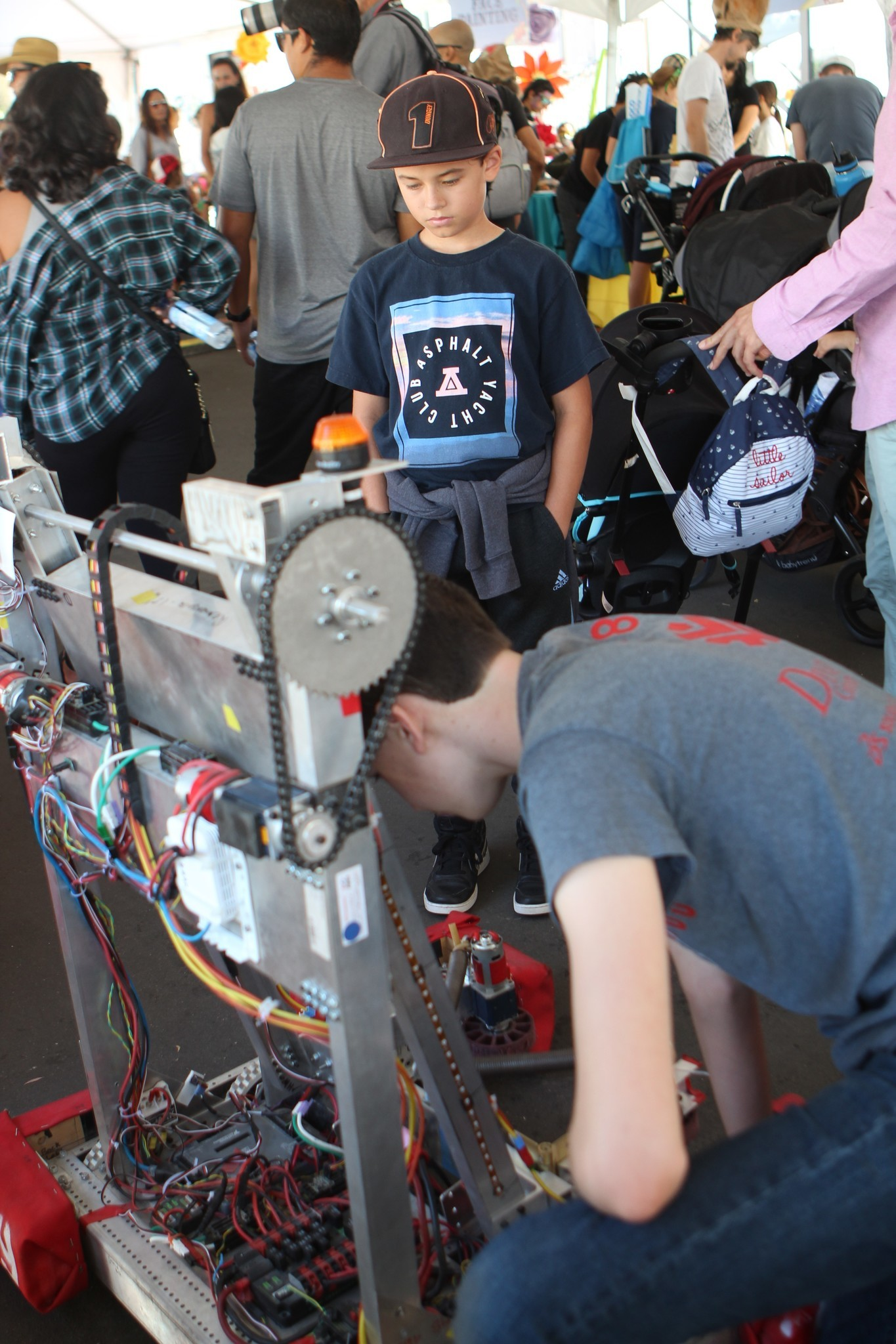 Aidan Farmer, 11, of Carmel Valley watches patiently as La Jolla High School junior Alex Gross tinkers with Veto the robot.