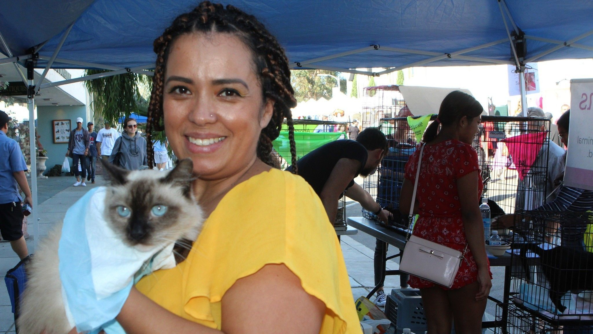 Decire Breidenbach of San Marcos adopts one of about 50 dogs and cats who found new homes during the festival's second adoption event.