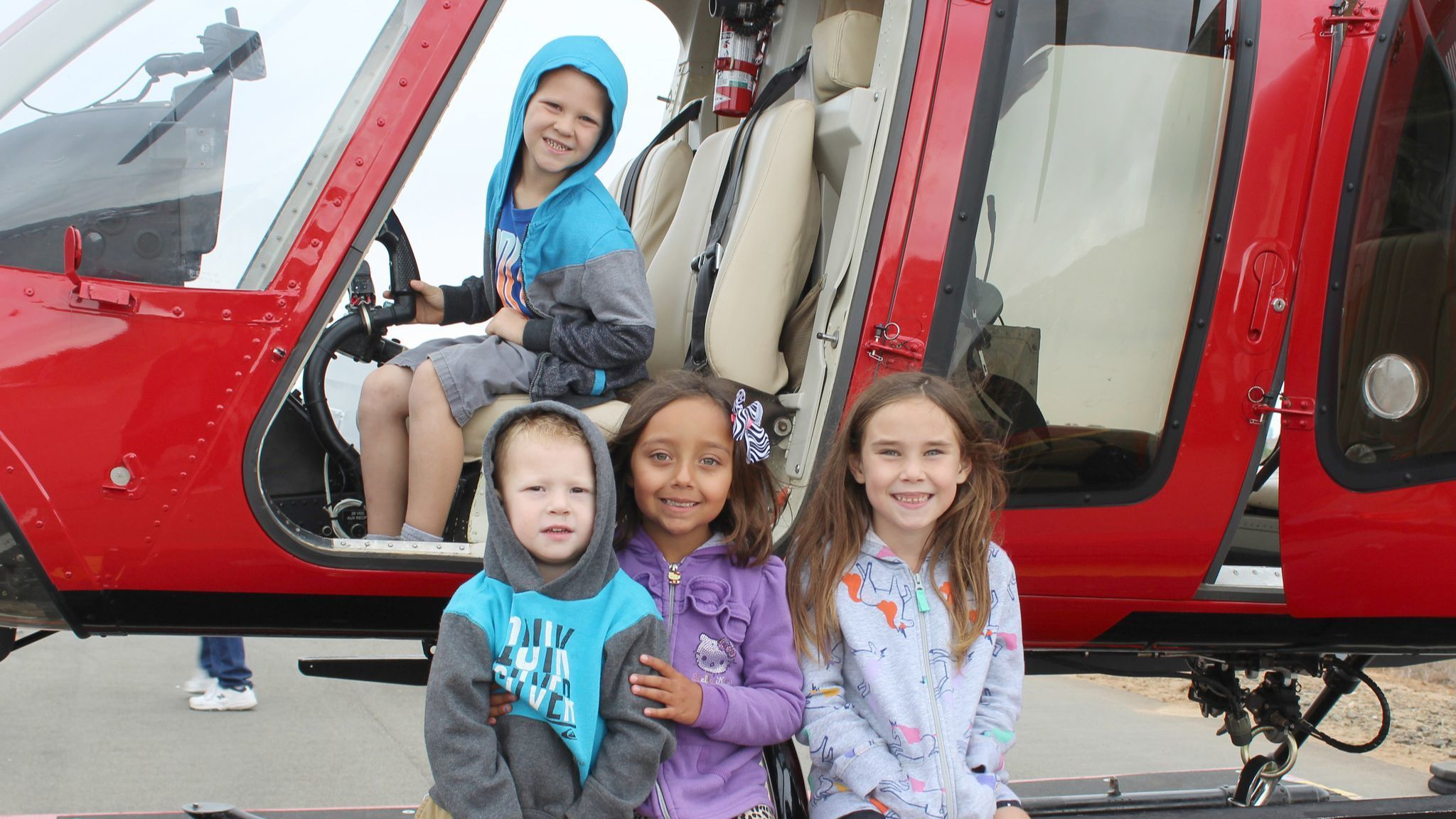 Ramona residents enjoy a pretend flight in a Bell 407 helicopter. Emmett Gooden sits in the cockpit and below, from left, are Dean Gooden, Adelynn Gooden, Christina Banegas-Krum.
