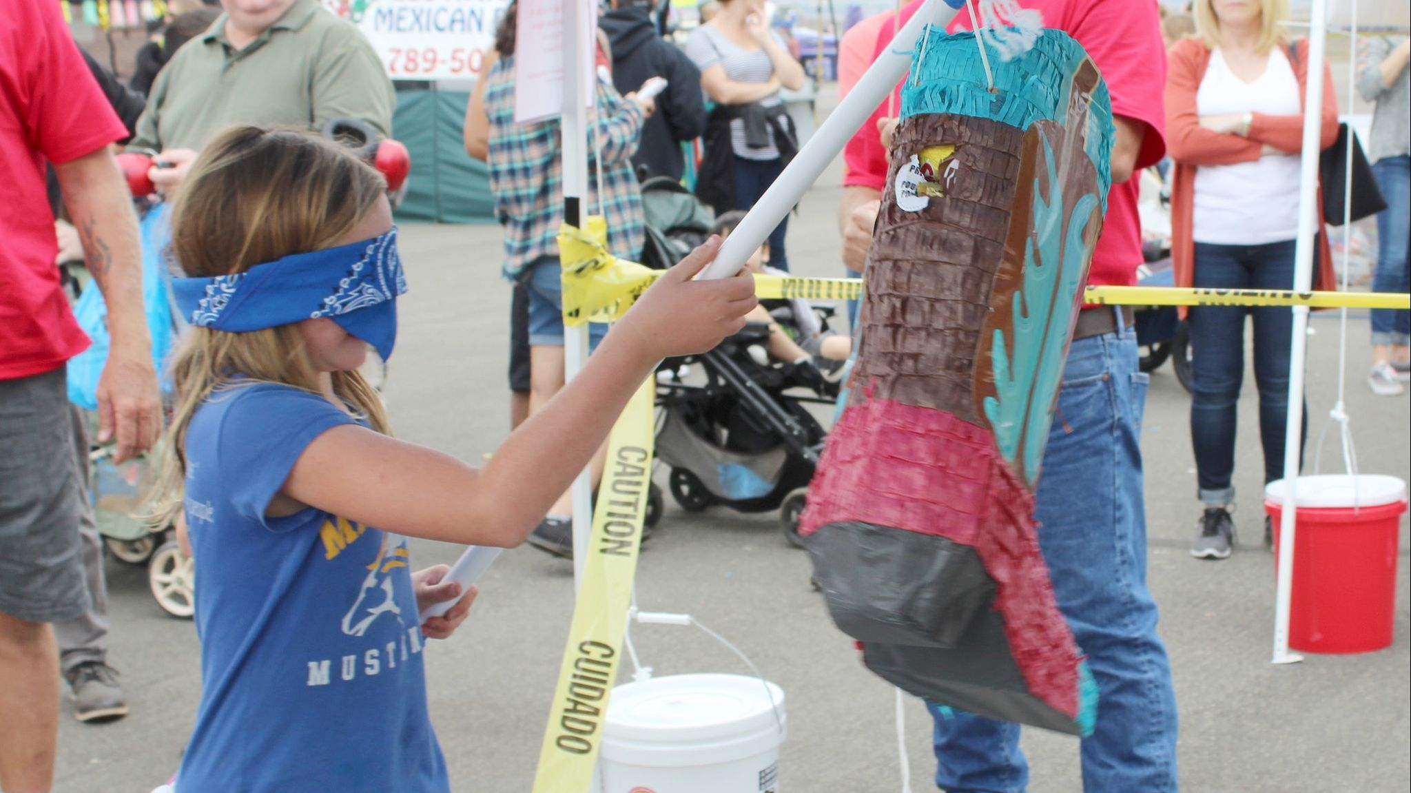 Nine-year-old Maggie Marrison takes a swing at the cowboy boot piñata shared at Ramona Airport's Air Fair & Fly-in.