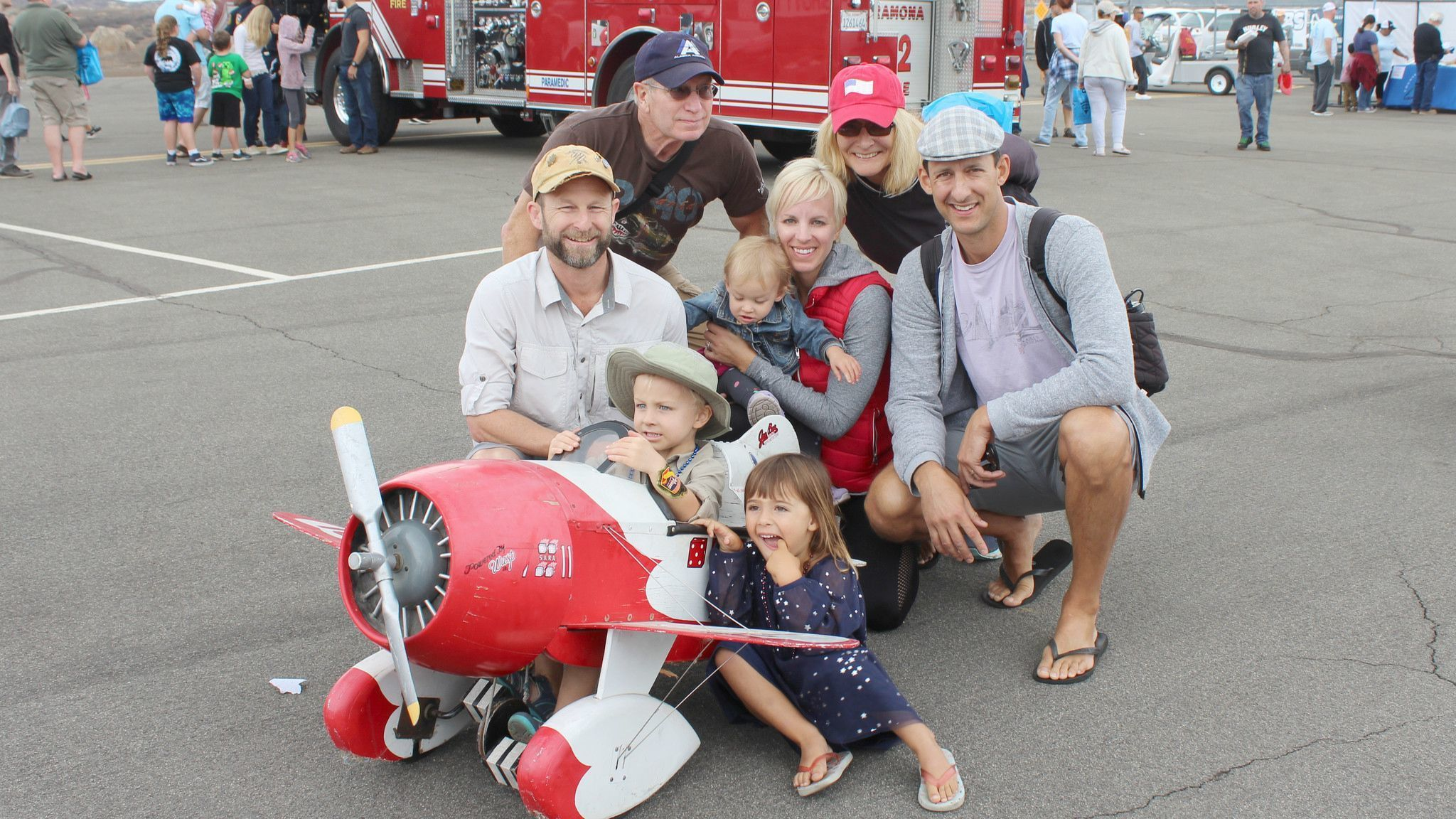 Wyatt Francis steers a miniature airplane with Stella Brodt and baby Annalisa Francis beside him. Onlookers are Jimmy and Nora Francis, John and Marlene Garrett, Christian Brodt.