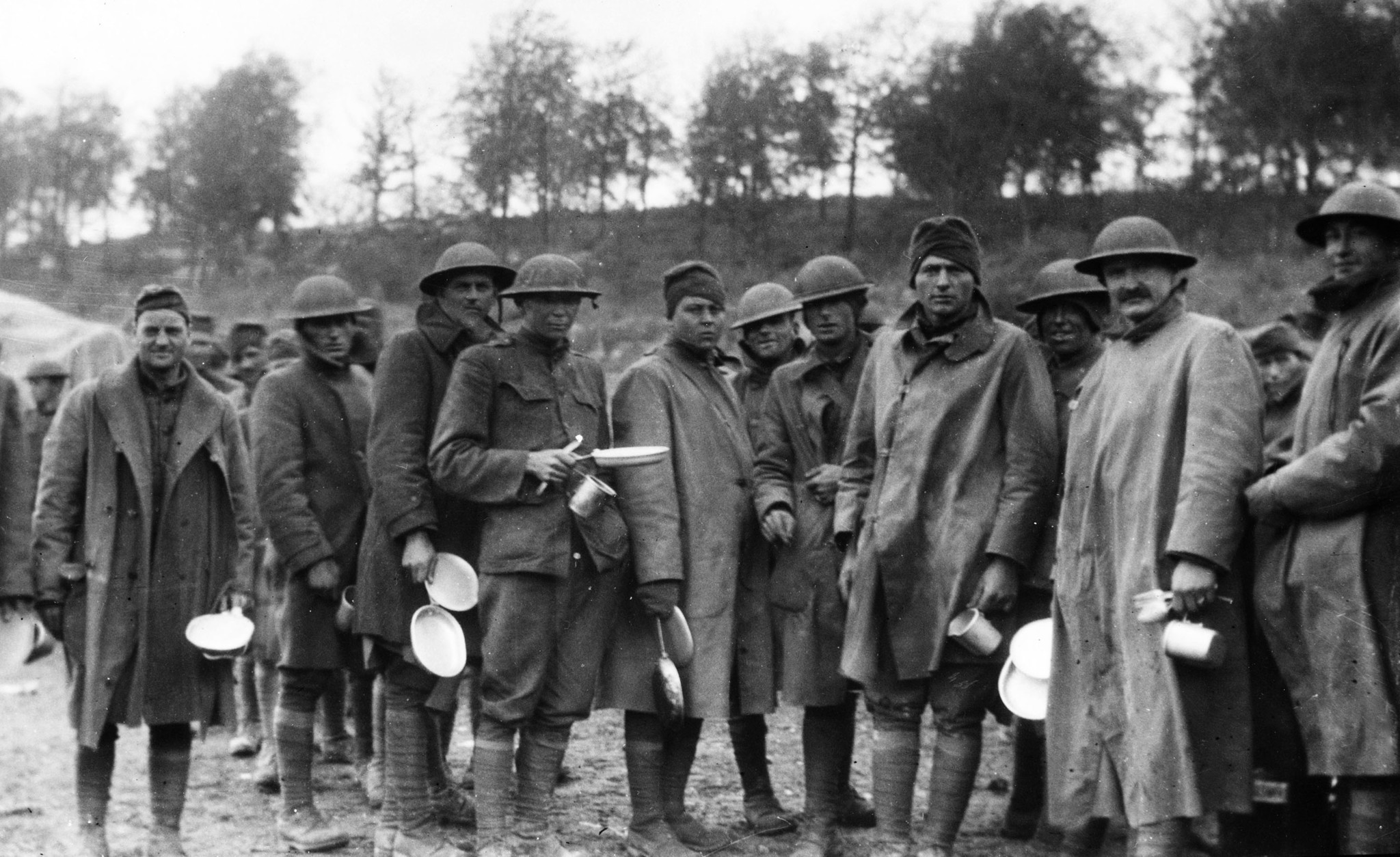 1918: Members of the 91st Infrantry Division, the Wild West Division, in early morning mess back nea