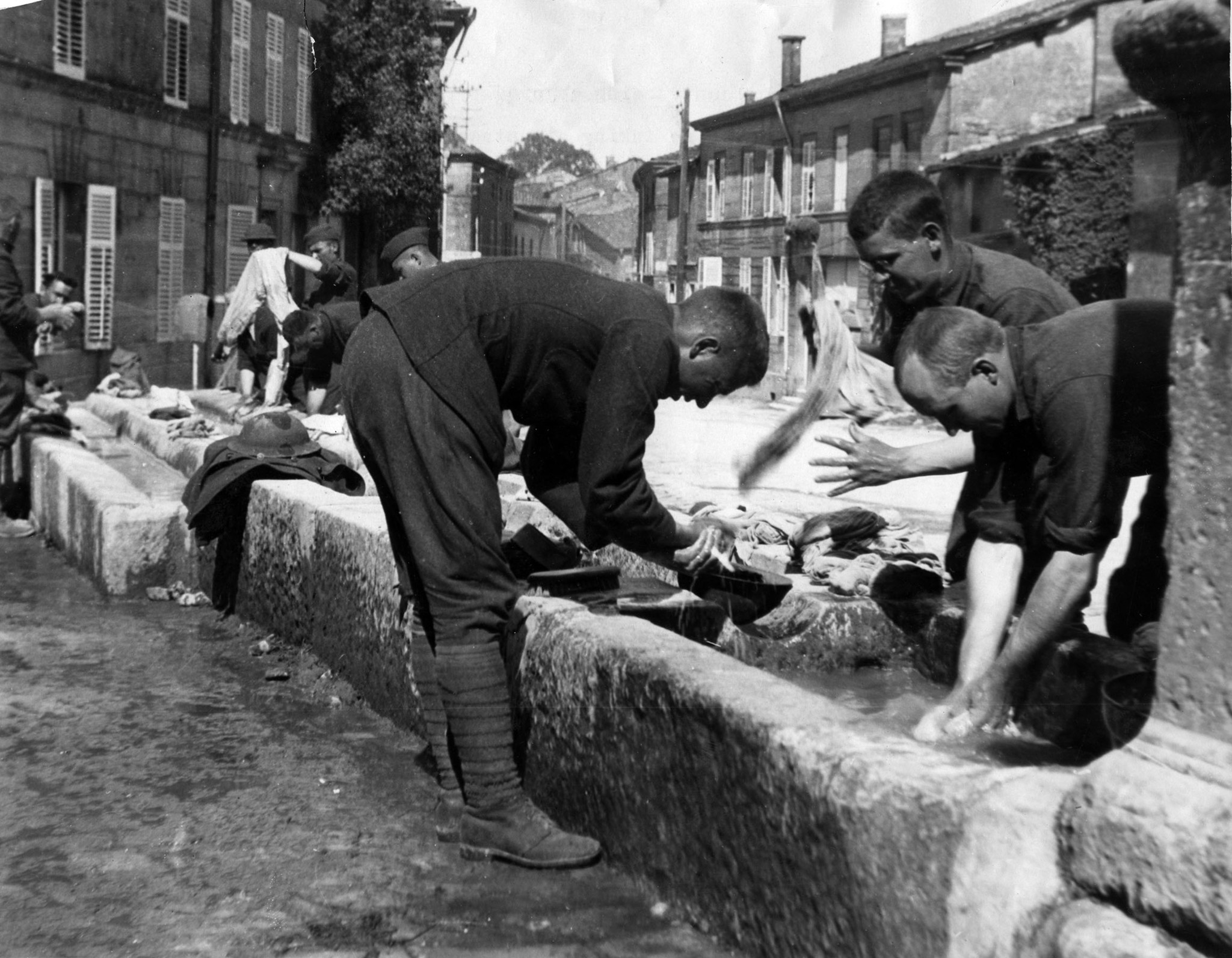 1918: Members of the 91st Infrantry Division take advantage of community washing troughs in village