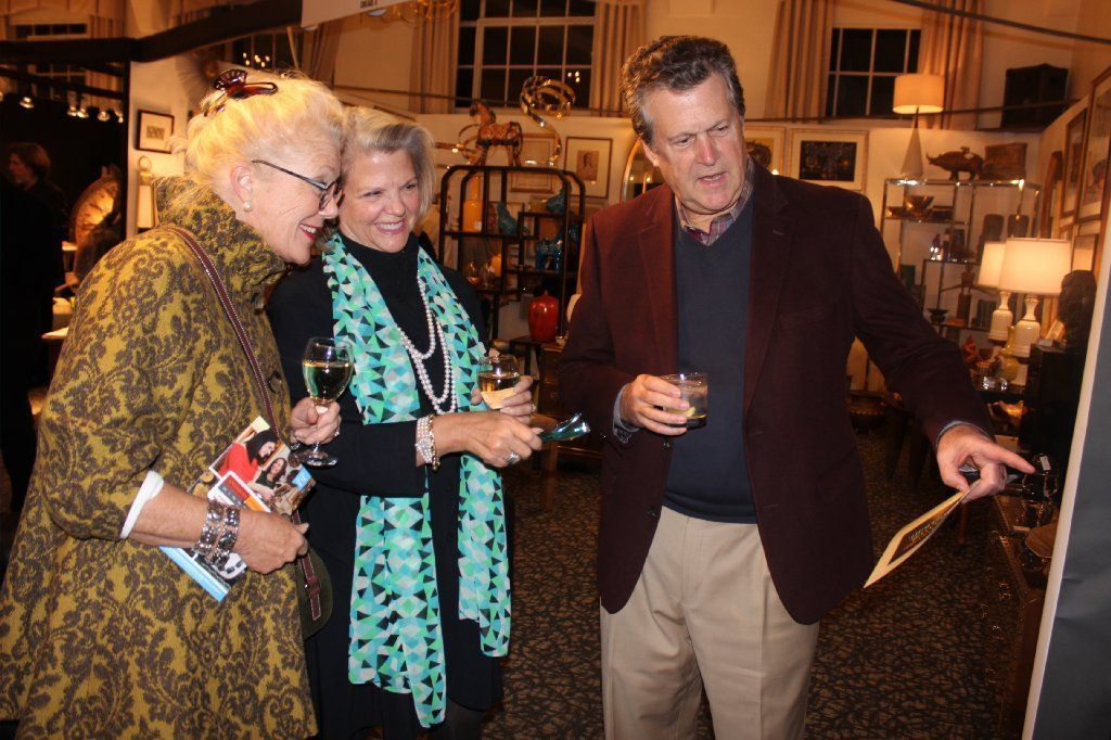 Ladd Mengel of Winnetka (from left) and Dana and John Hagenah of Wilmette peruse artwork.