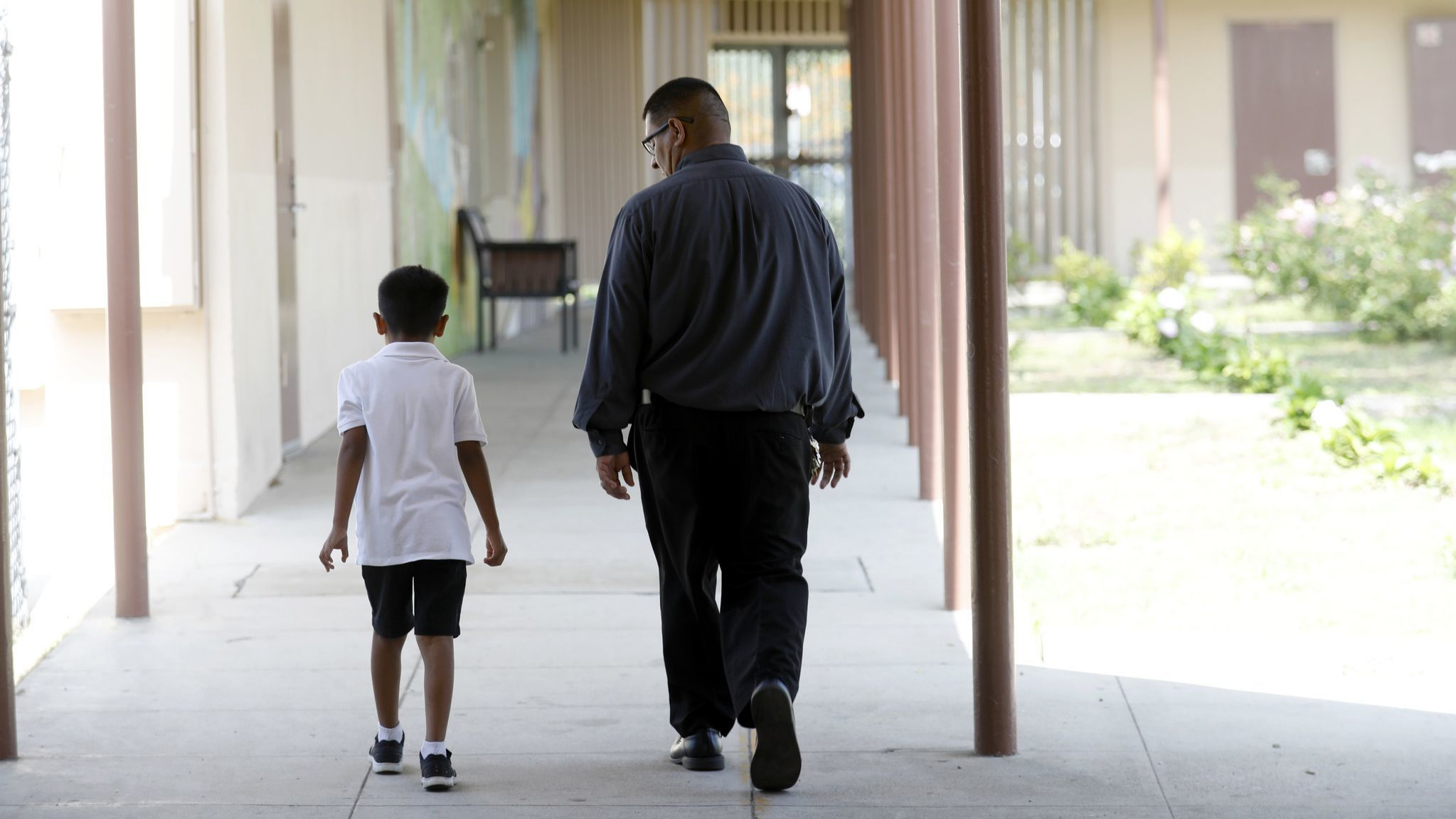 Principal Jose Razo walks with a student