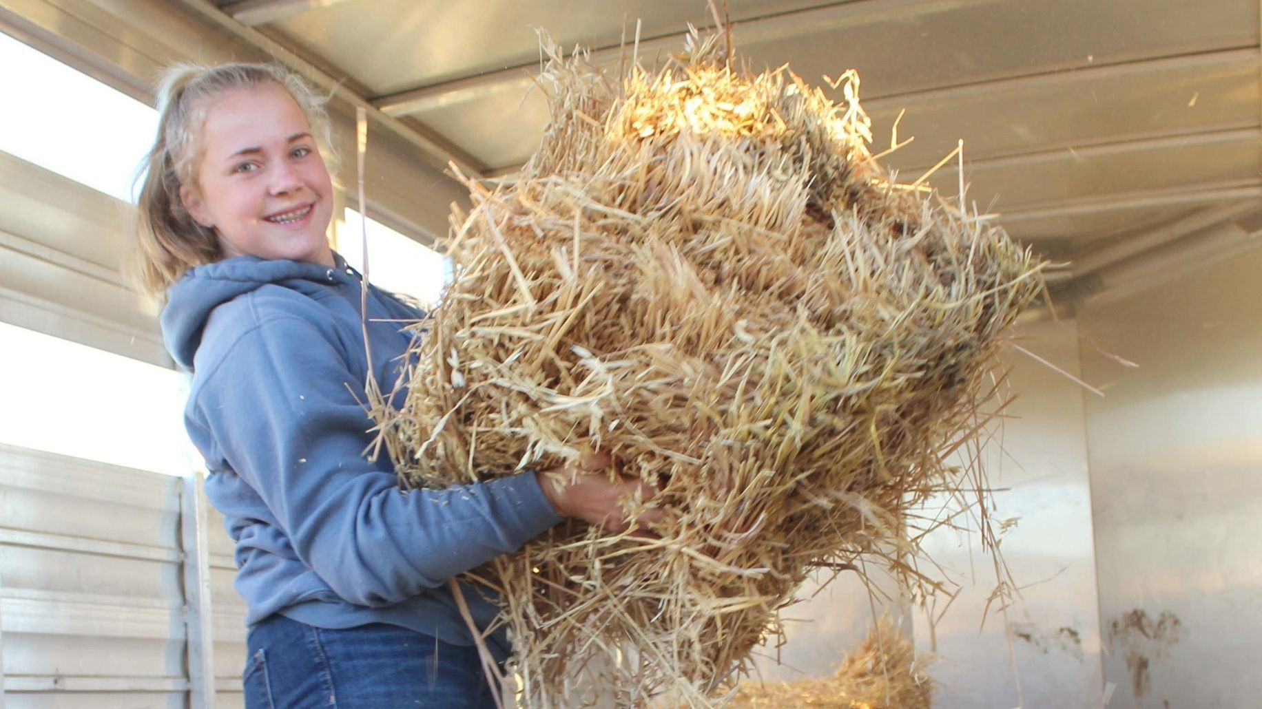 Eighth-grader Morgan Nelson loads hay onto a truck.