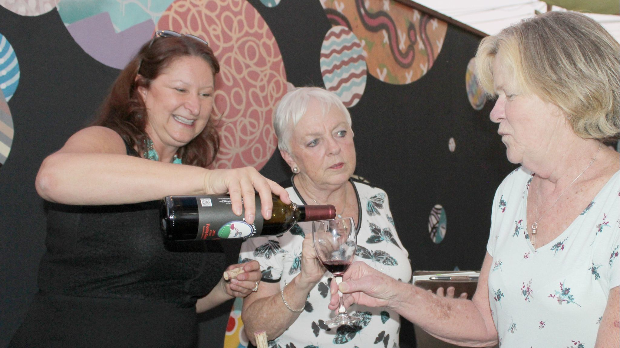 Elaine Lyttleton, center, co-chair of the 6th Annual Art & Wine Festival, talks with Vicky James of Ramona as Teri Kerns of Ramona Ranch Vineyard & Winery pours a glass of wine.