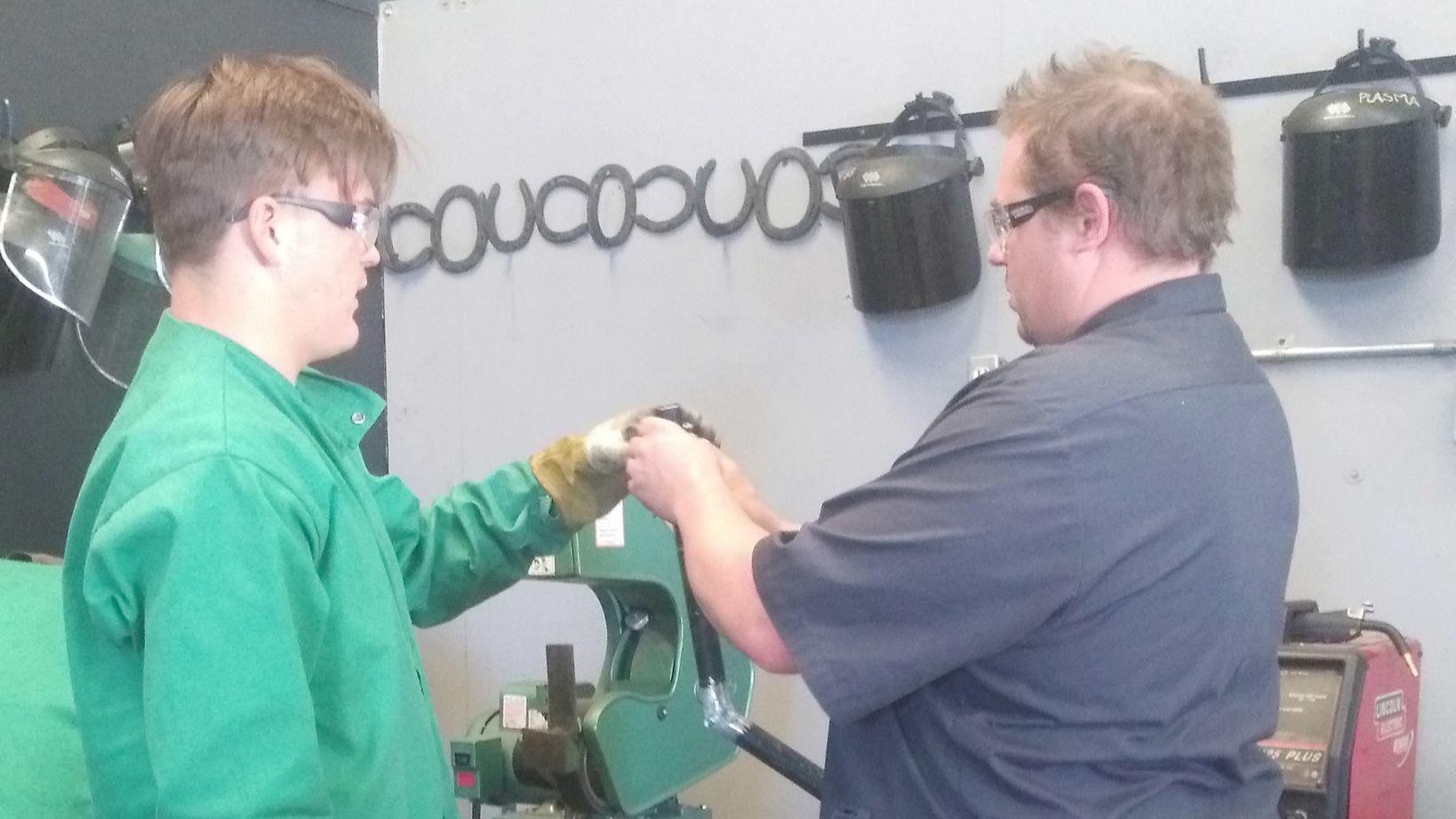 Ramona High sophomore Bryan Schreiber, left, gets advice from welding teacher Matthew Funkhouser.
