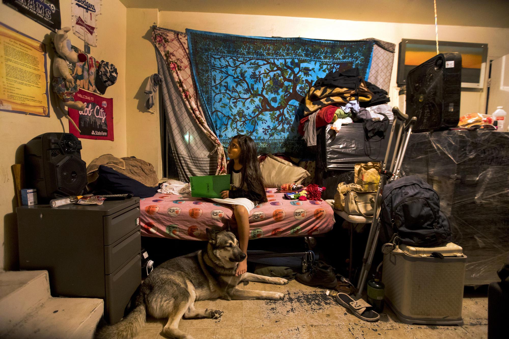 Angelina Orellana does homework in a garage