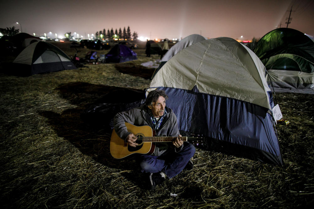Chris Yarbrough, who lost his home in the Camp fire, plays a donated guitar in a tent city set up by evacuees in a Chico parking lot.