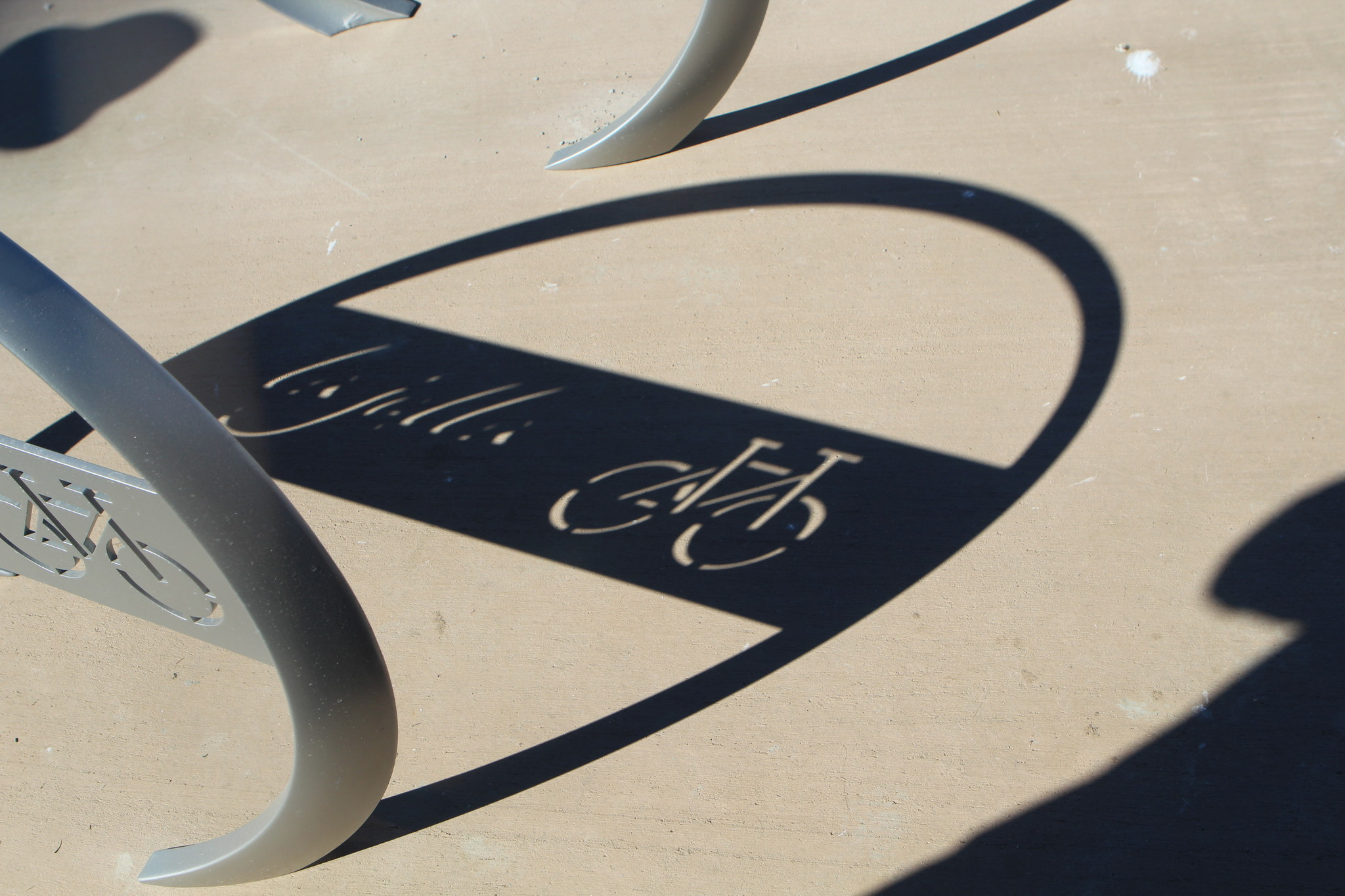 Each bike rack consists of five grey partial circles of metal embedded into concrete.