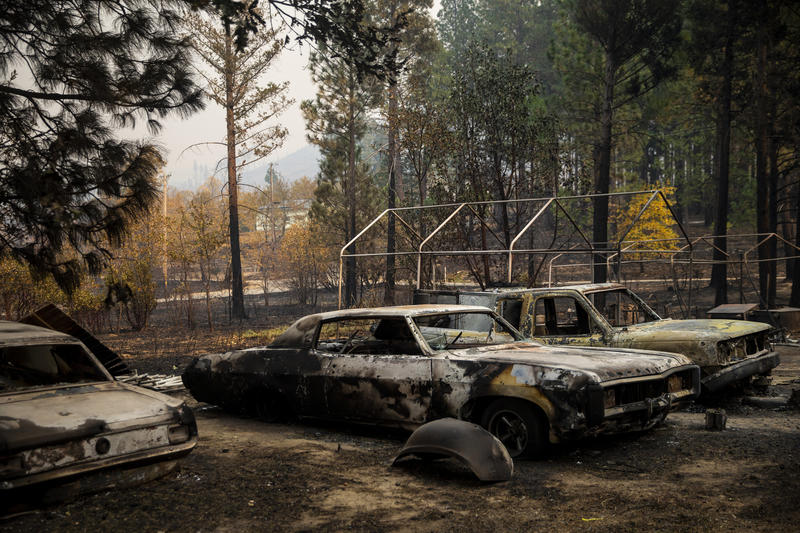 Cars destroyed by the Camp fire sit outside a home along Yana Trail.