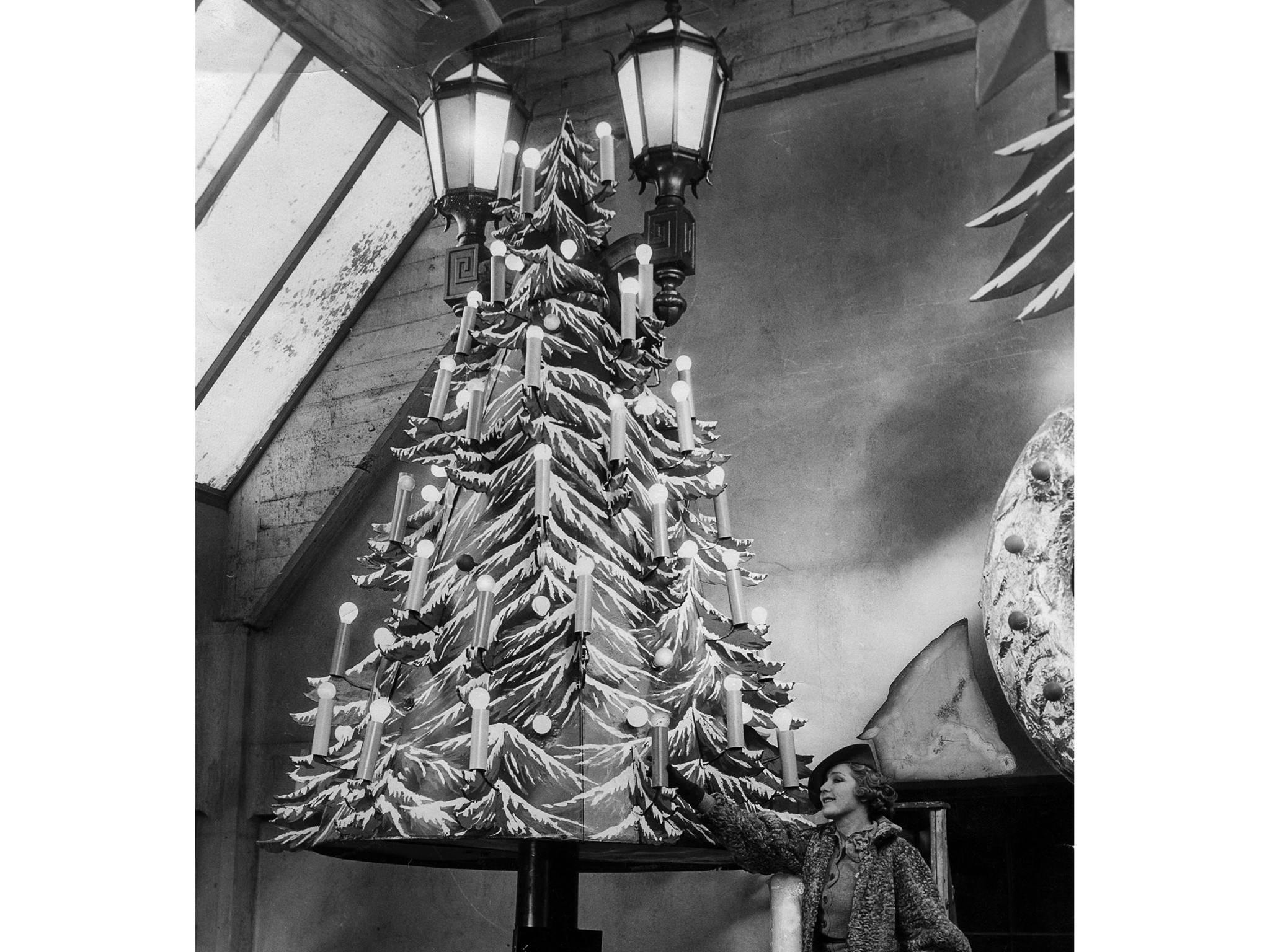 Nov. 16, 1935: Actress Mary Pickford poses next to one of the Christmas trees decorations that will