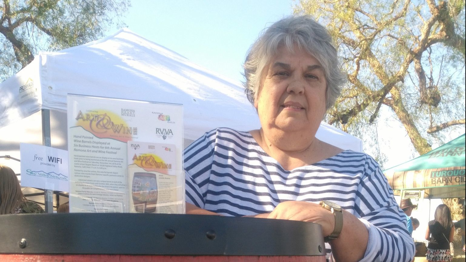 Artist Lynette Bredow displays the wine barrel she painted depicting historic Ramona scenes. The high bid of $2,700 came from attorney Bob Krysak.