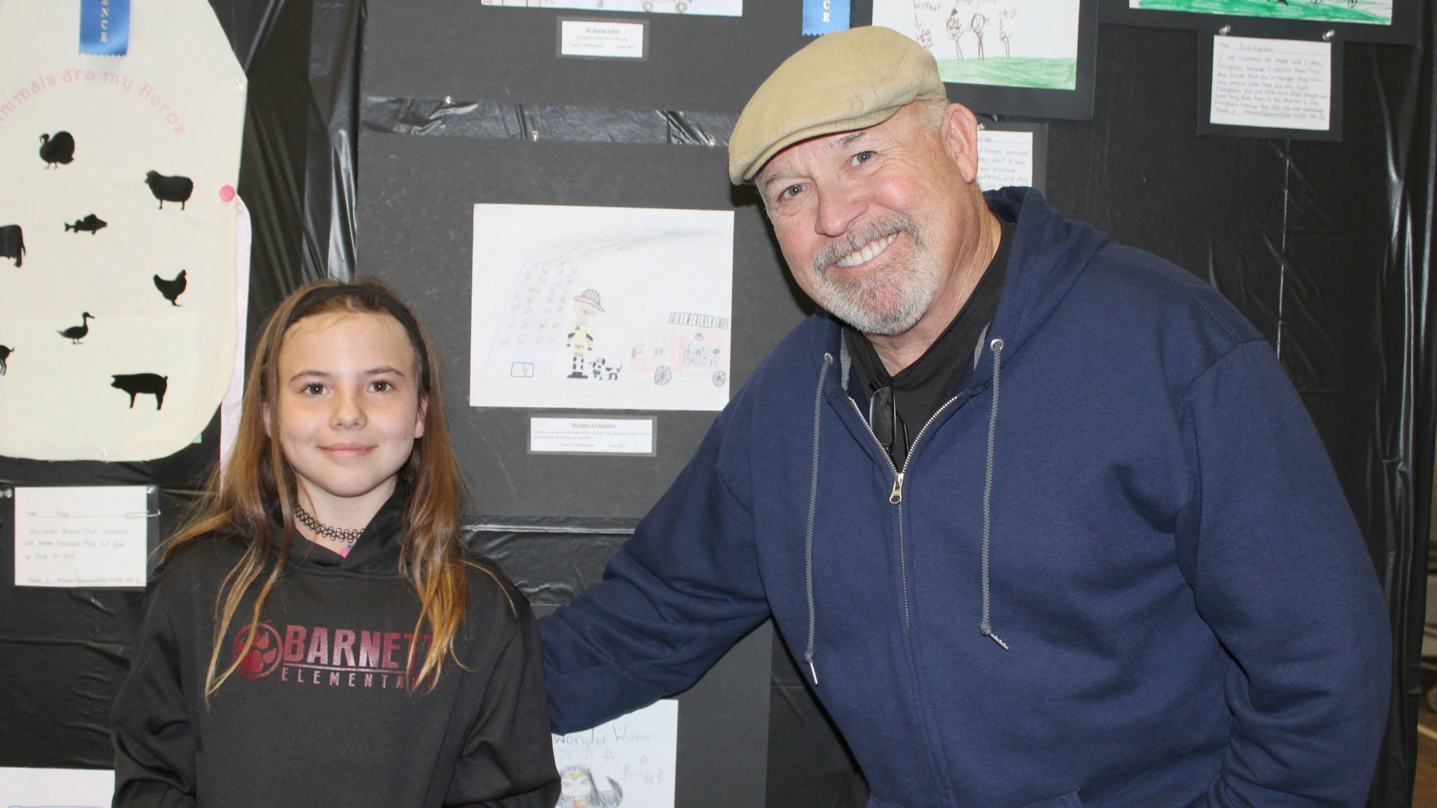 "Barnett Elementary third-grader Quinn Archer and her grandfather, retired firefighter Gary Buchholz, stand by Quinn's Reflections entry titled ""My Papa/A Firefighter."""