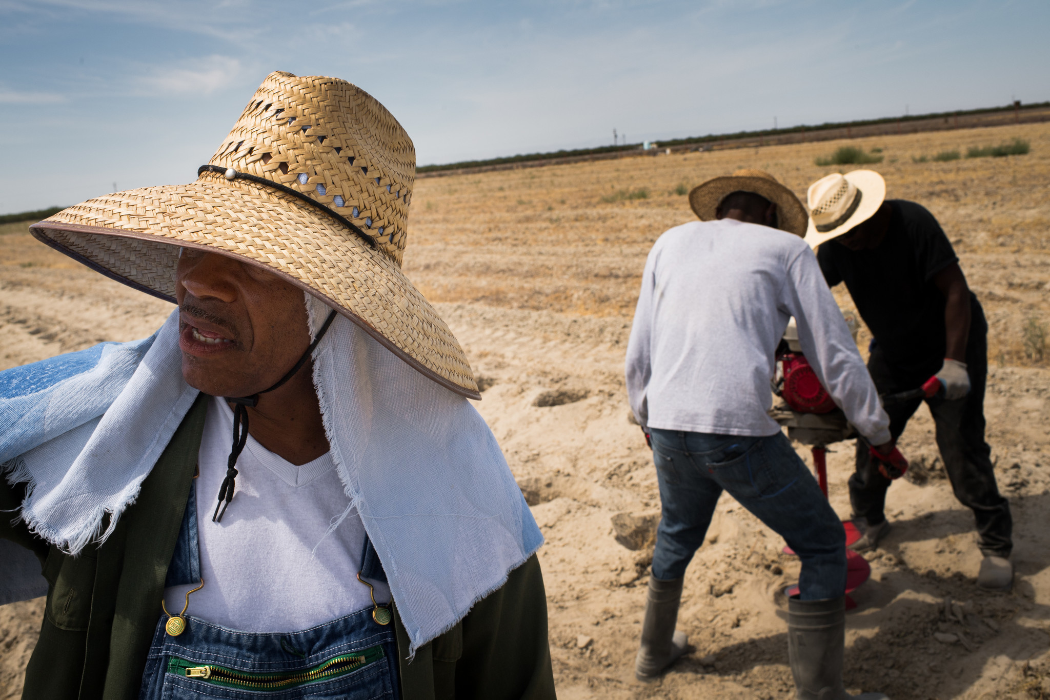 Dennis Hutson directs two of his farmworkers as they auger holes for trees to act as a windbreak on