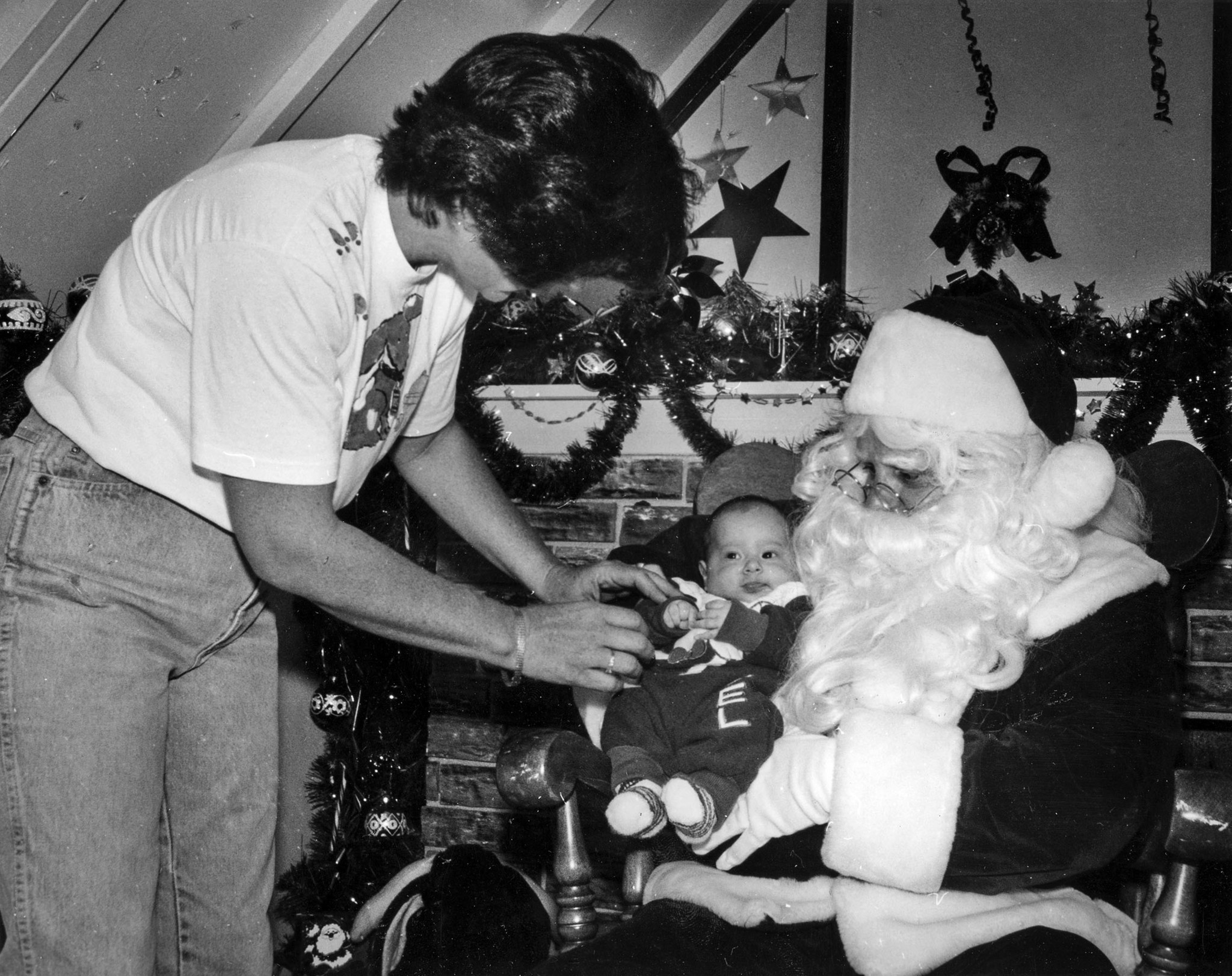 Dec. 8, 1990: Photographer Muriel Wuethrich positions 2-month-old Sergio Maya on Santa's lap before t